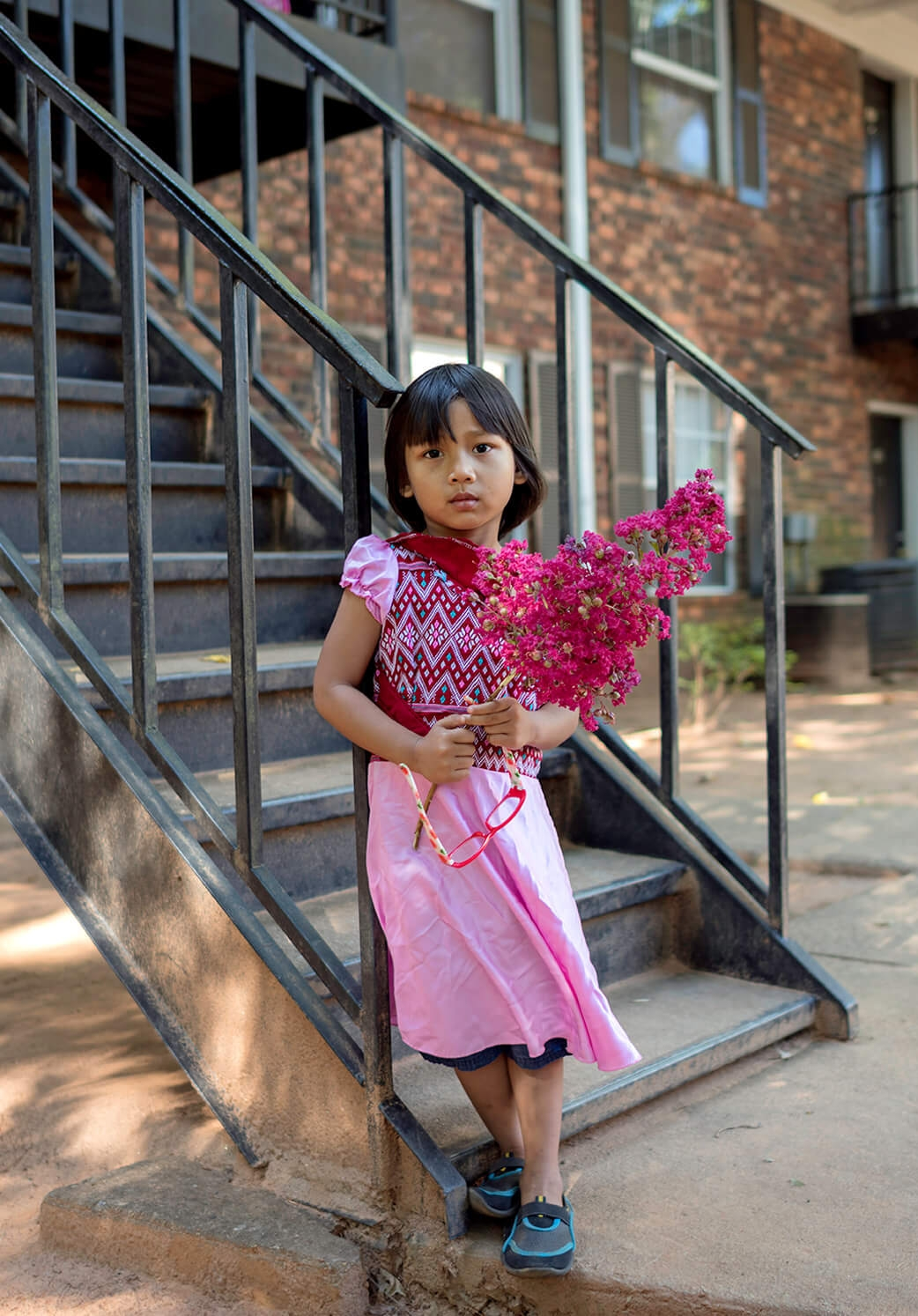 A young girl holds the branch of a Crepe Mrytle tree. Her family fled violence in Burma and they have been living as refugees in Clarkston for over three years.