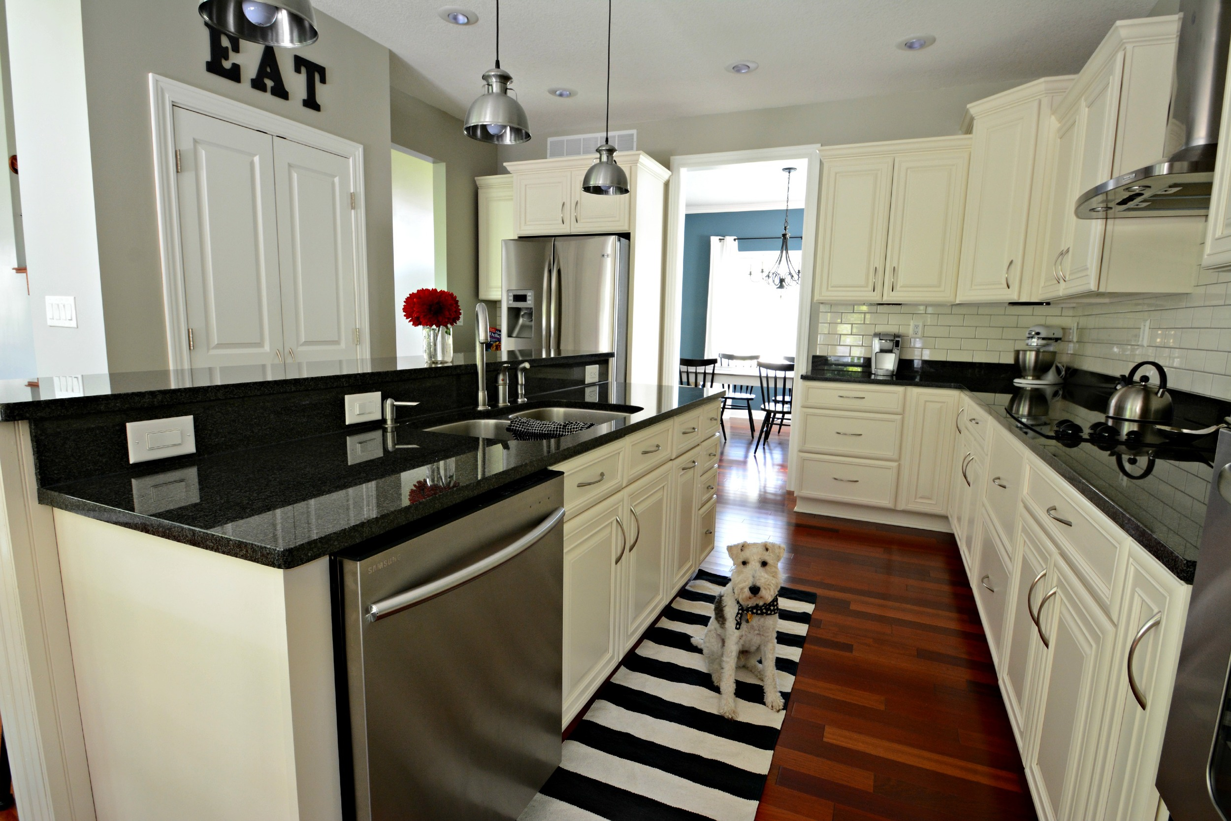 Sherwin Williams Mindful Grey. Subway tile with dark grout. Black Granite. Ivory Cabinets. Industrial Lights.