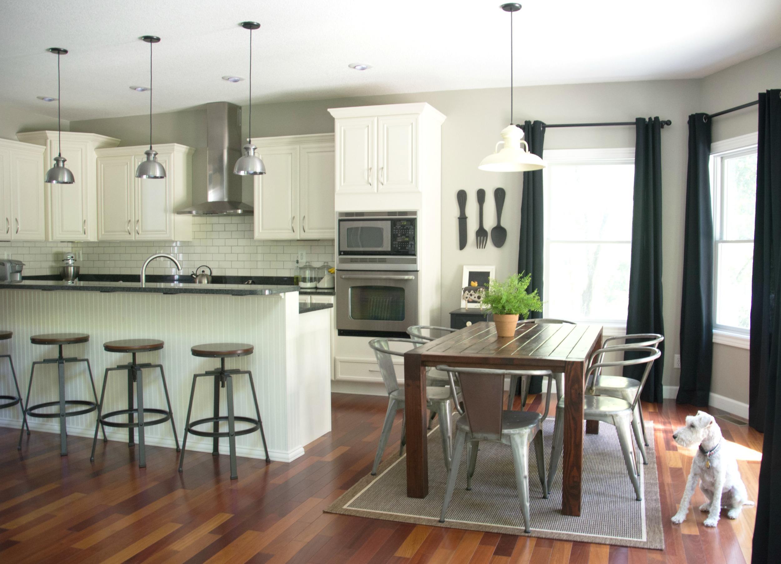Black curtains.  Black granite. Ivory cabinets. Farmhouse table.  Barnlight lighting.