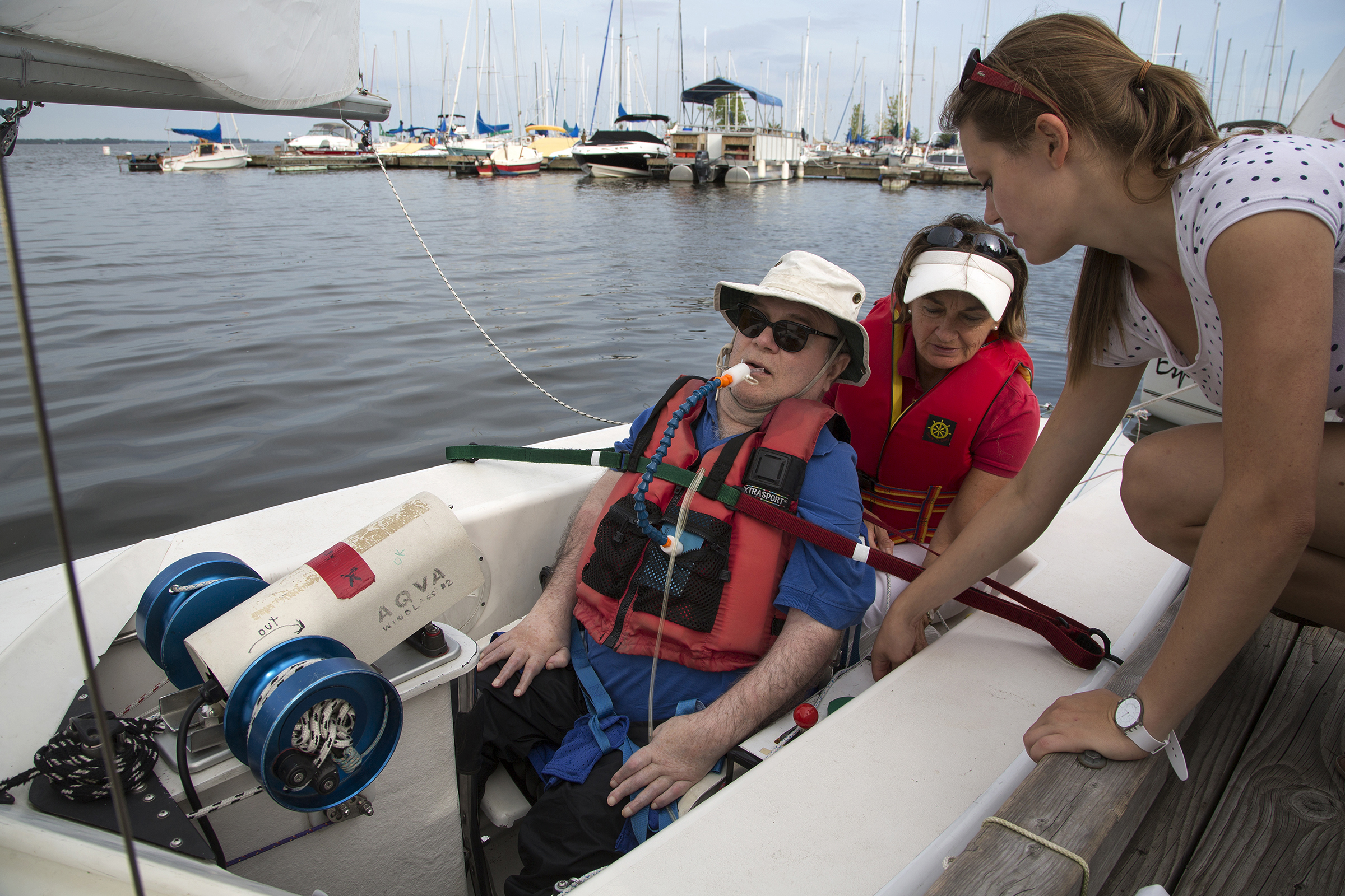 POINTE-CLAIRE, QC. AUGUST 20, 2014 -- Skipper René Dallaire, a quadriplegic and Executive Director of Association québécoise de voile adaptée, is secured into a sailboat at the Pointe Claire Yacht Club in the West Island of Montreal, along with Senneville mayor Jane Guest on Wednesday, August 20, 2014. (Leslie Schachter/West Island Chronicle,  Transcontinental )