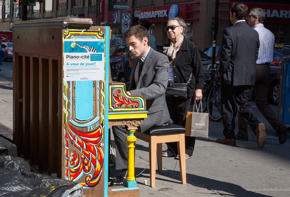MONTREAL, QC. October 1, 2013 -- Nicolas Jolicoeur entertains passers-by at one of Montreal's public pianos, part of the borough of Ville-Marie's Piano-Cité program, on Ste-Catherine St on Tuesday, October 1, 2013.  (Leslie Schachter/unpublished)