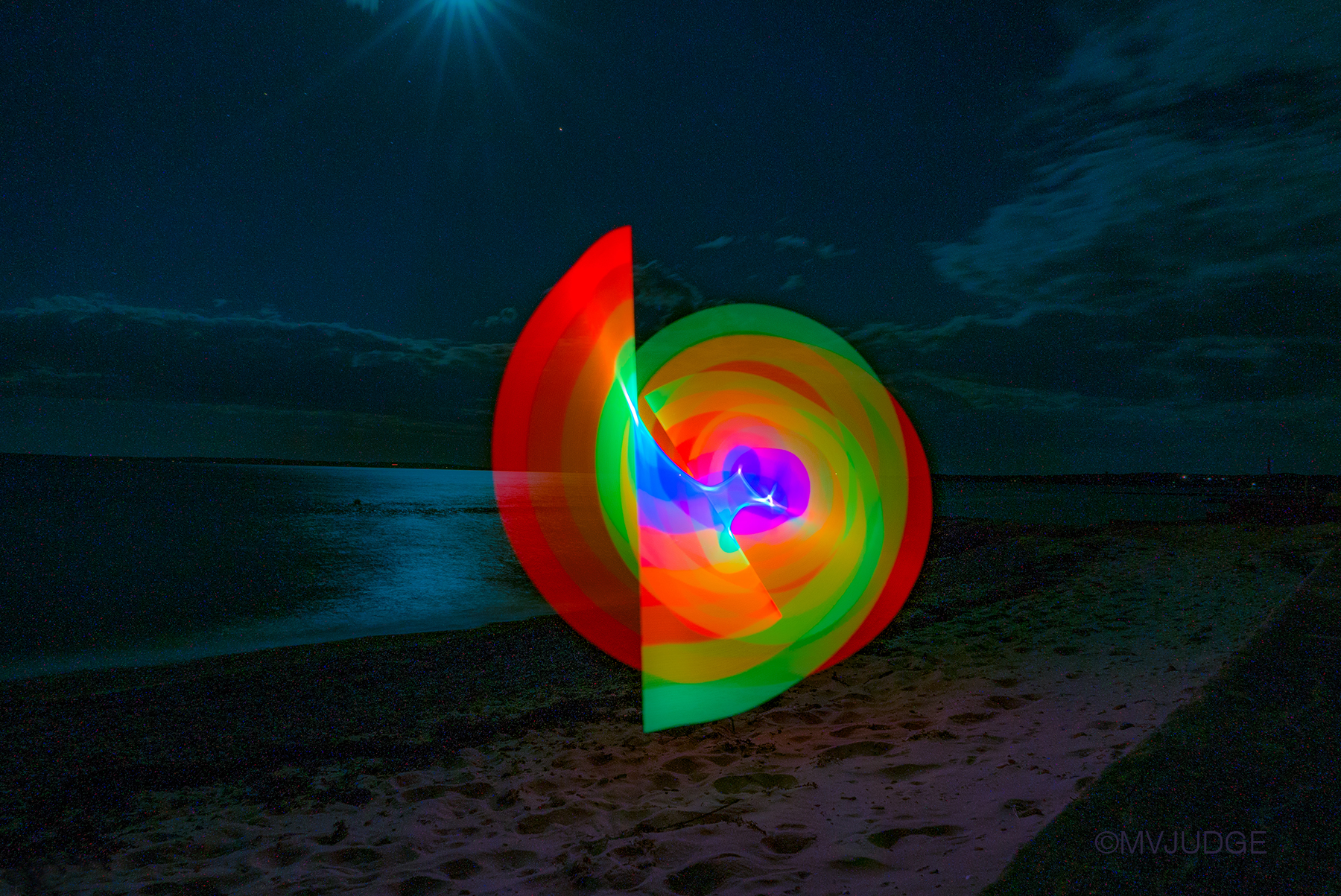 """""""swirl""""   mvjudge©2016  The """"Rainbow Lights the Dark"""" series was created a week after the Orlando nightclub shooting. The beauty of the full moon and the Cape Cod beach reminded me as I swirled the rainbow lights, that the victims, so many young lives, will never enjoy another full moon, or a beach, or the joy of creating and sharing their vision with the world. Each time I look through these photos I'm stricken with grief, and hope that we all can wave our rainbow in unity and pride.  All rights reserved @mvjudge 2016"""