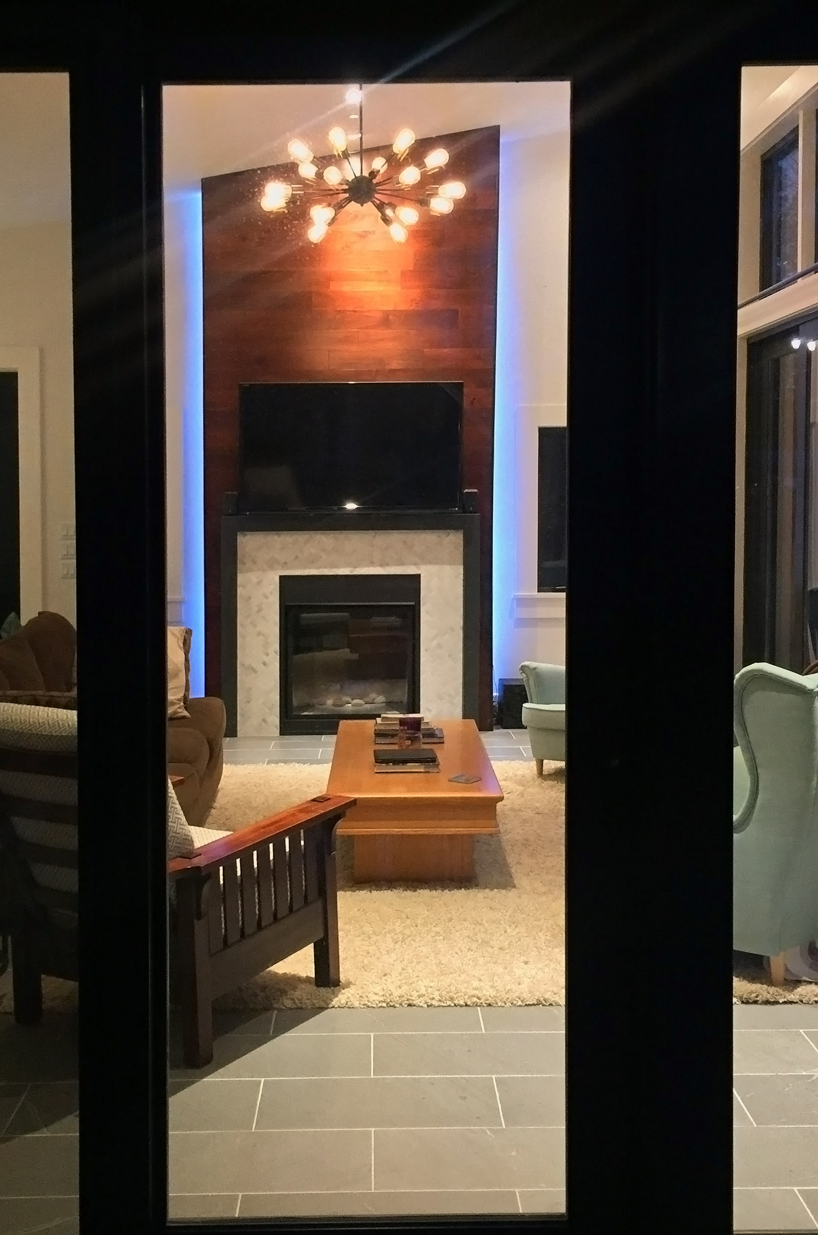 Floor to ceiling backlit fireplace feature.