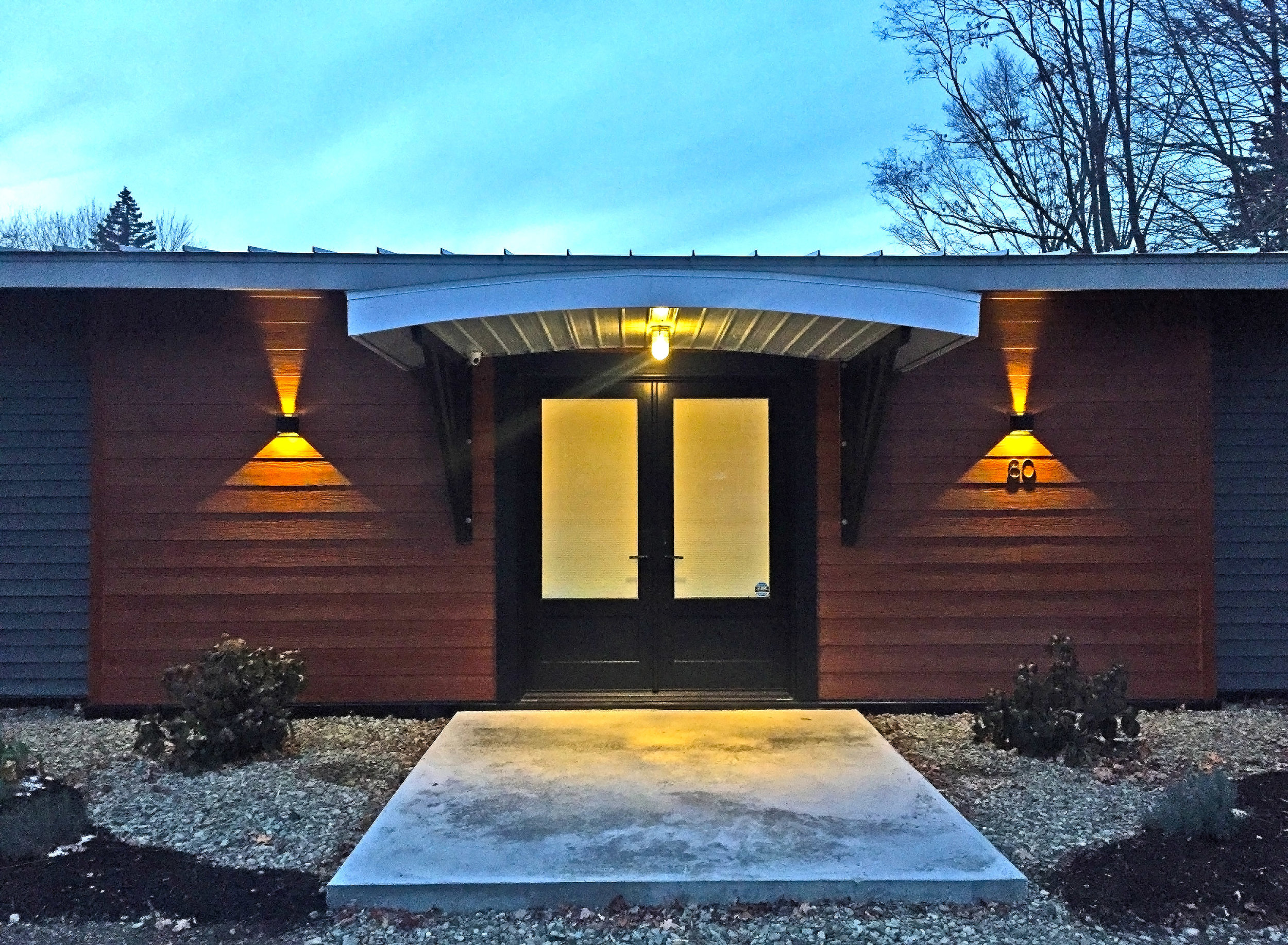 Custom bracketed canopy over double door entry facing the road.