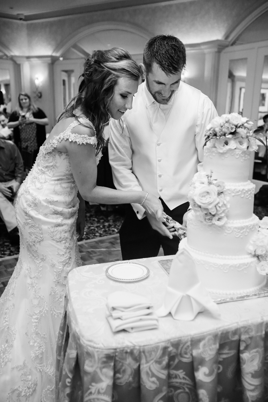 Bride and groom cutting wedding cake black and white photo