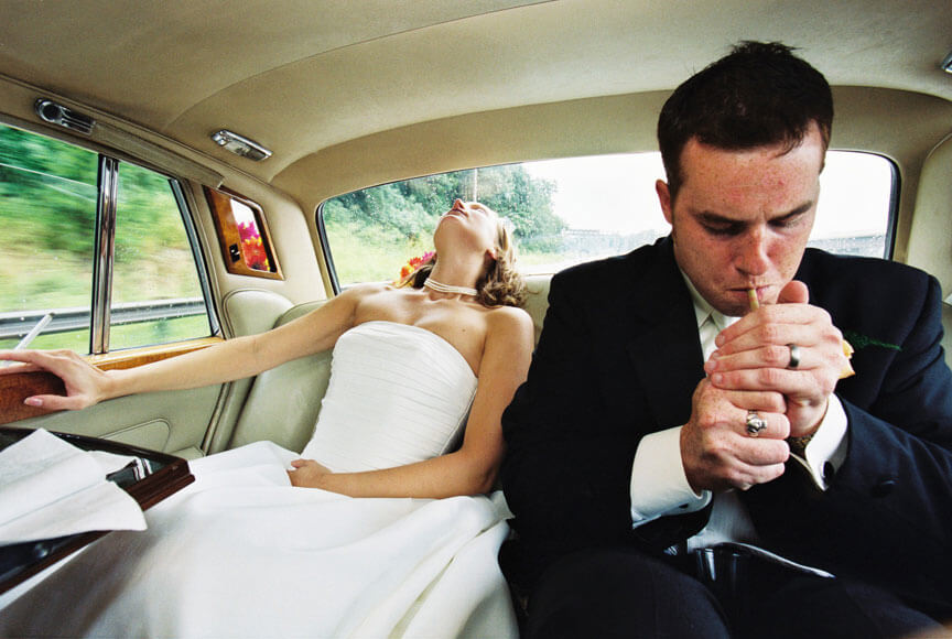 Documentary or Photojournalism wedding photo bride and groom after ceremony smoking in limo