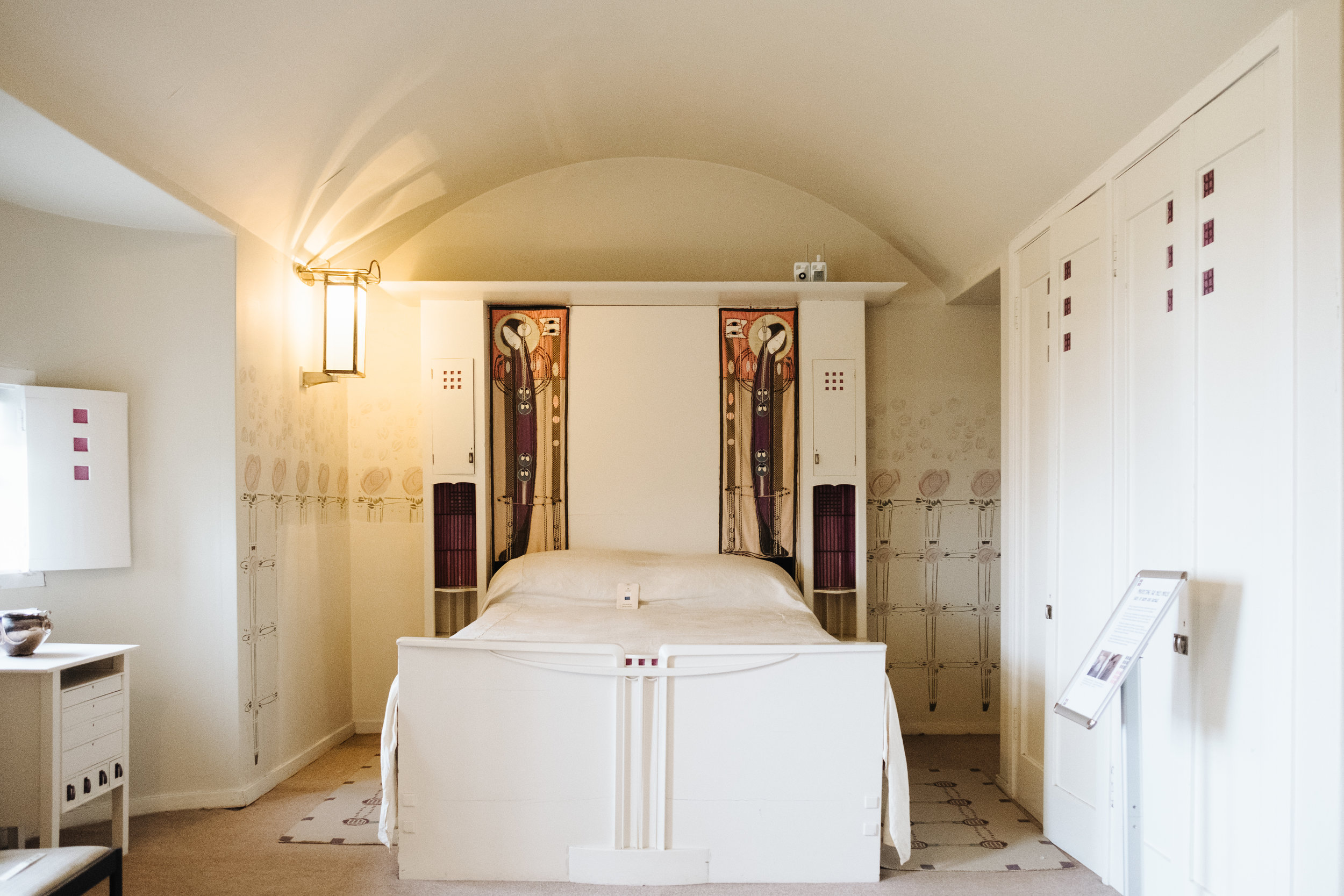The small shuttered window in the curved recess next to the bed conjures up romantic imagery associated with fairytale castles.