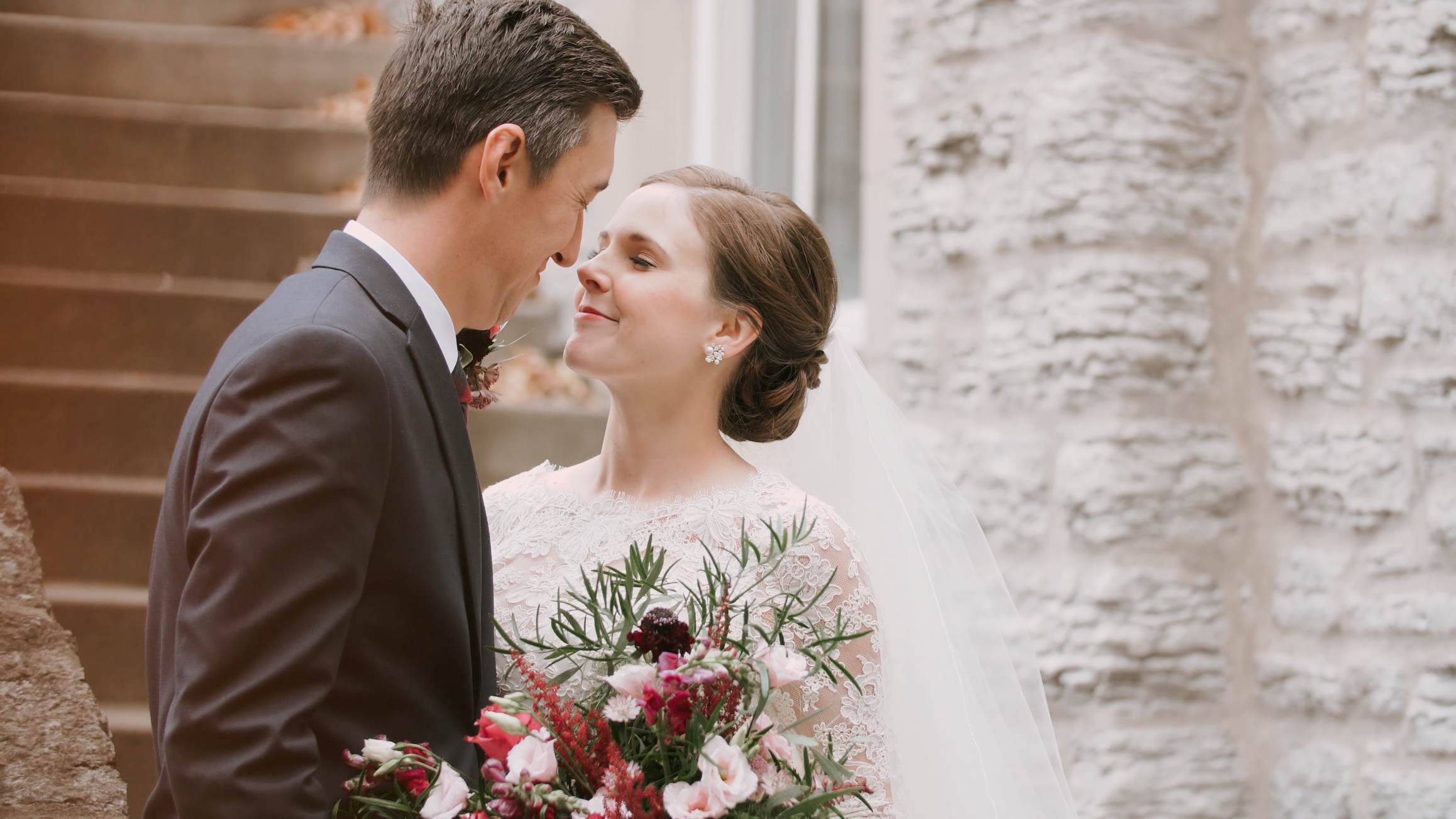 Kevin and Kate looking into each other's eyes in front of beautiful stone wall at the Semple Mansion