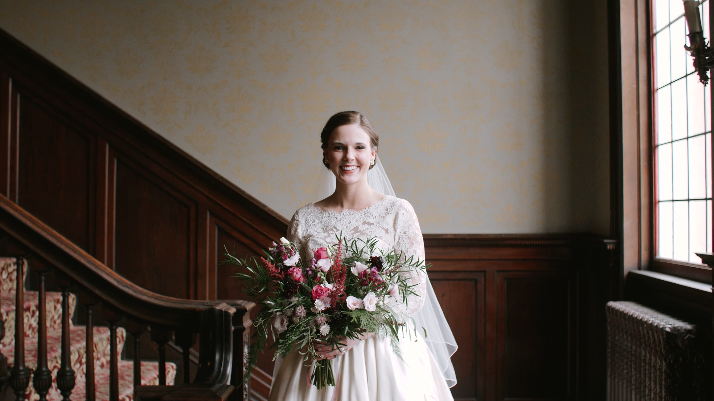 Kate holding bridal bouquet near steps and window with natural lighting.