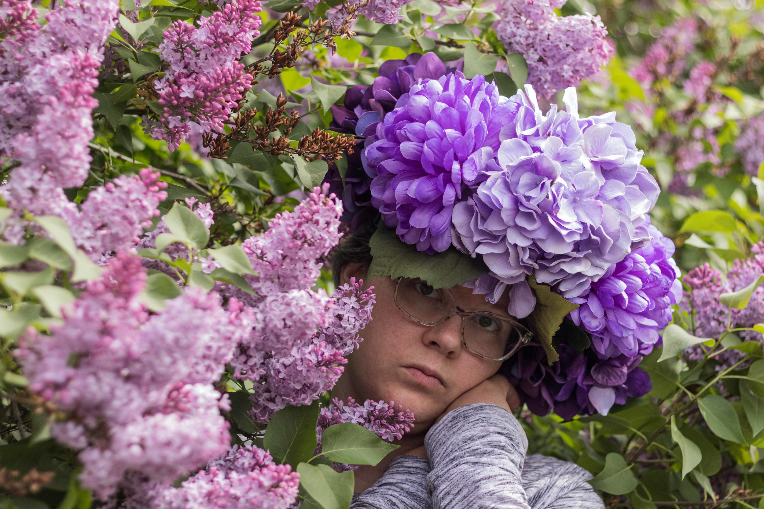 My recent selfie with my purple faux flower crown and the blooming lilac hedge.