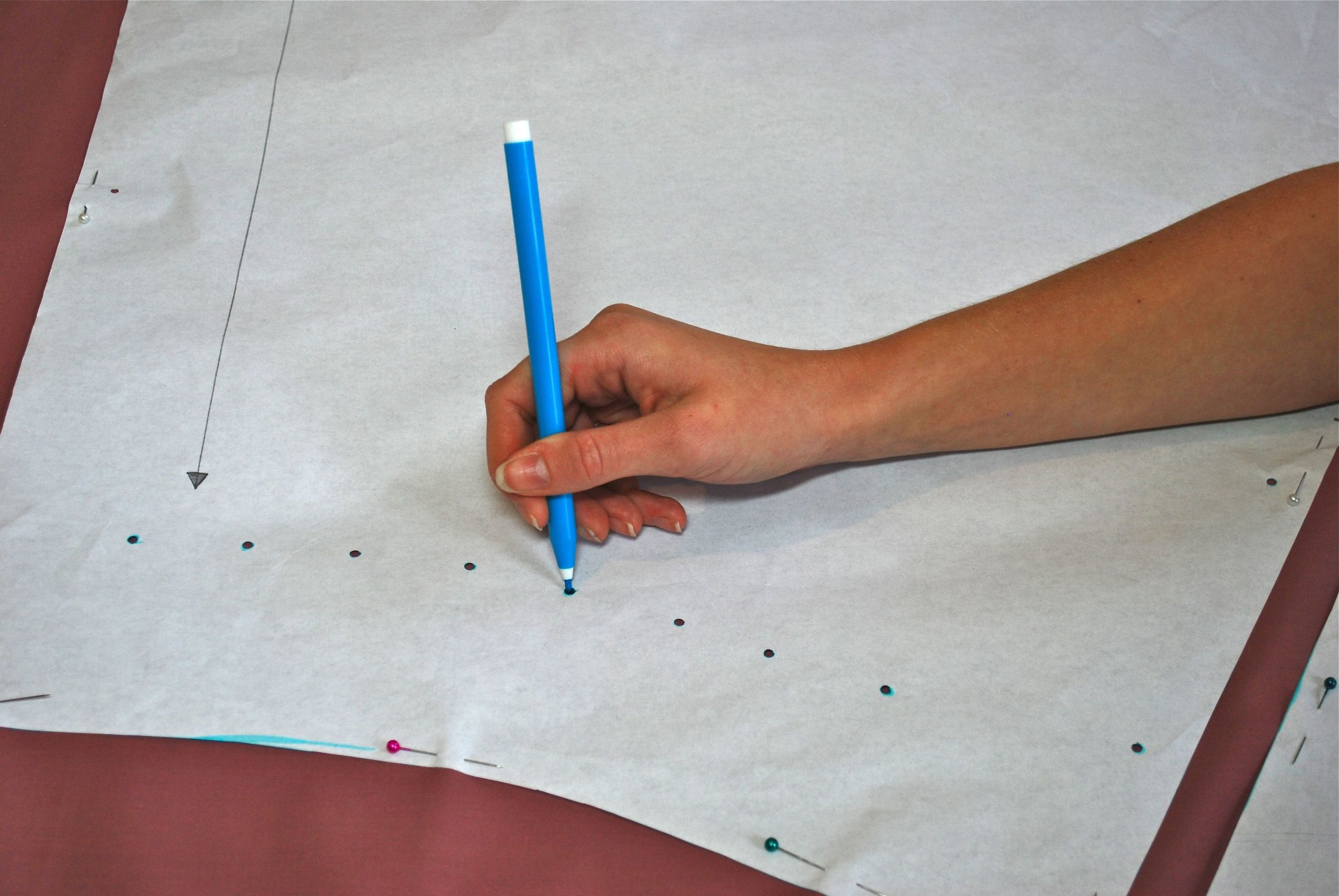 Marking out pleats on Naomi's pattern pieces. We punched holes thorough the small circles that were on the pattern, then stuck our pen through the holes to mark the fabric.