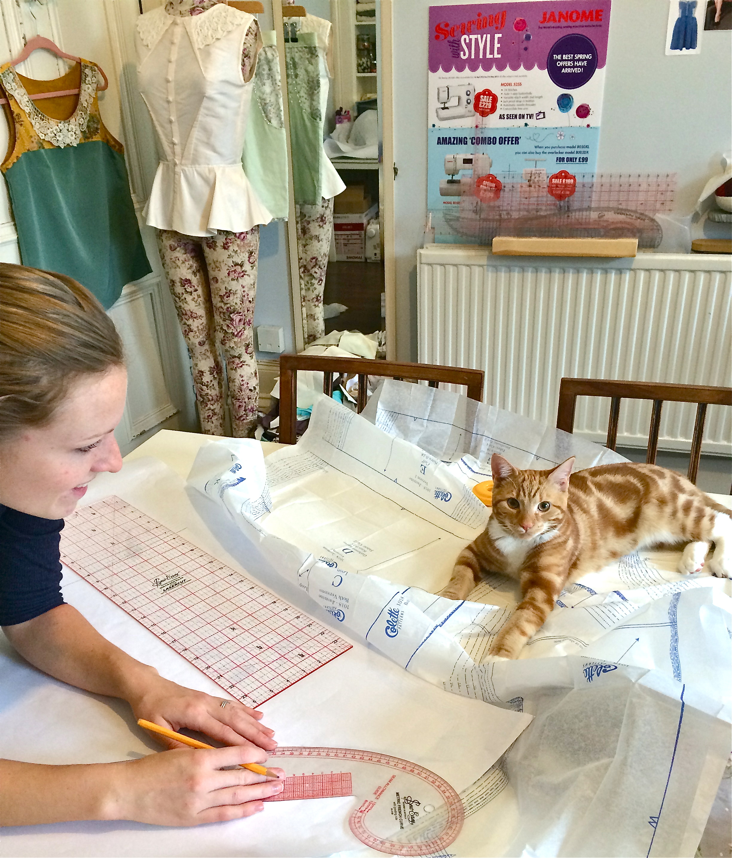 Naomi, with Lars the Cat, tracing out her Zinnia pattern pieces
