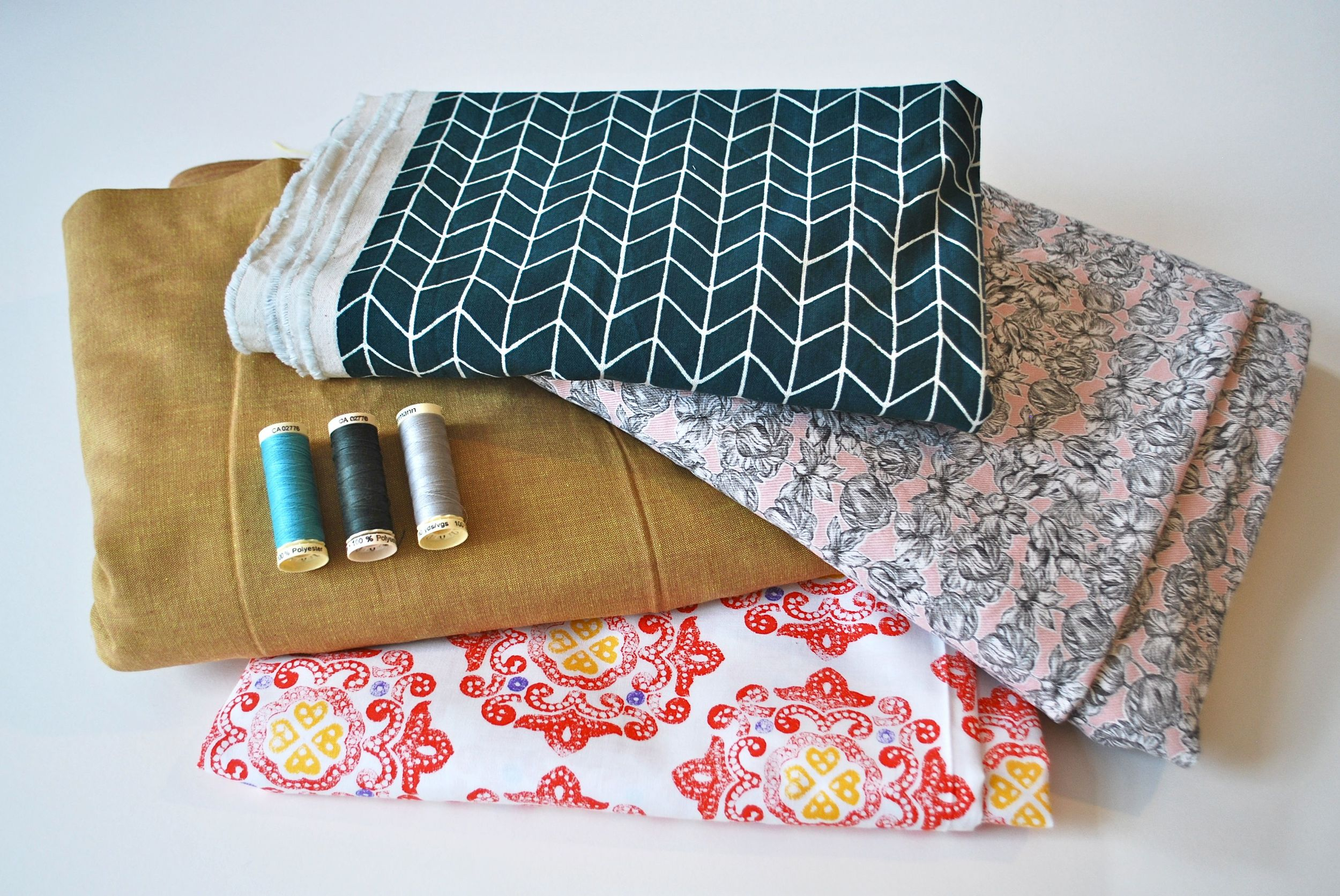 Cotton fabrics with different prints and some Gutterman threads of different colours.