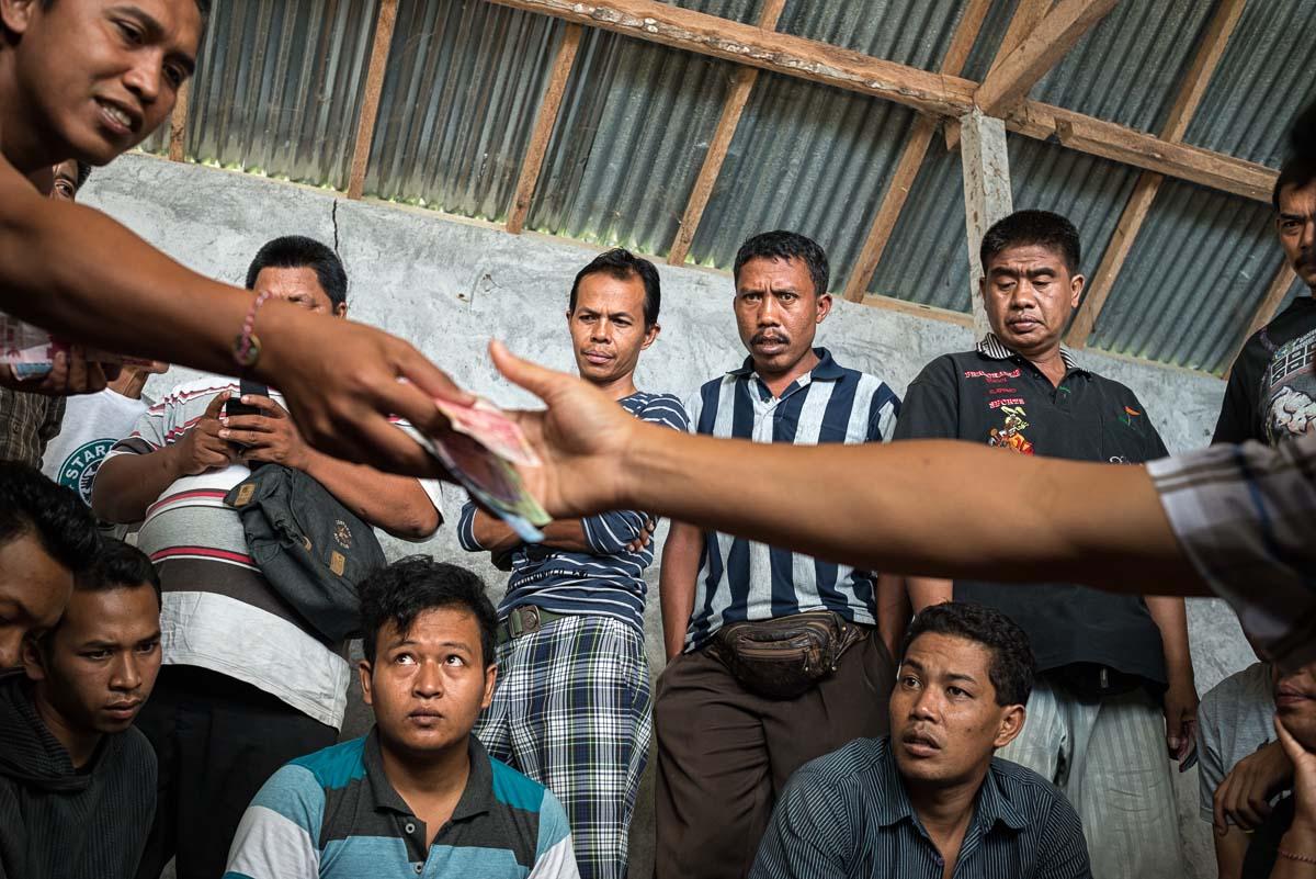 Tajen spectators taking part in small stake games before proper betting starts.