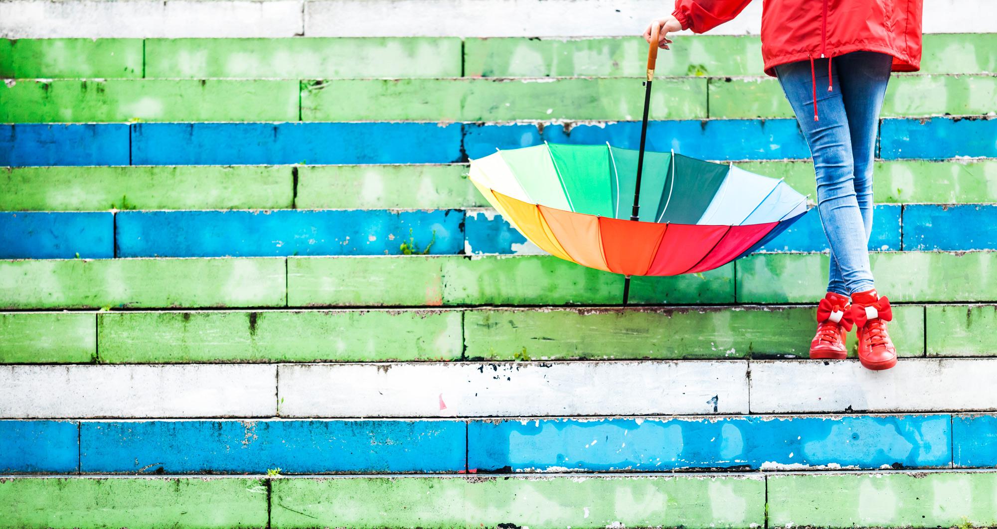 woman_holding_multicolor_umbrella_in_the_rain.jpg