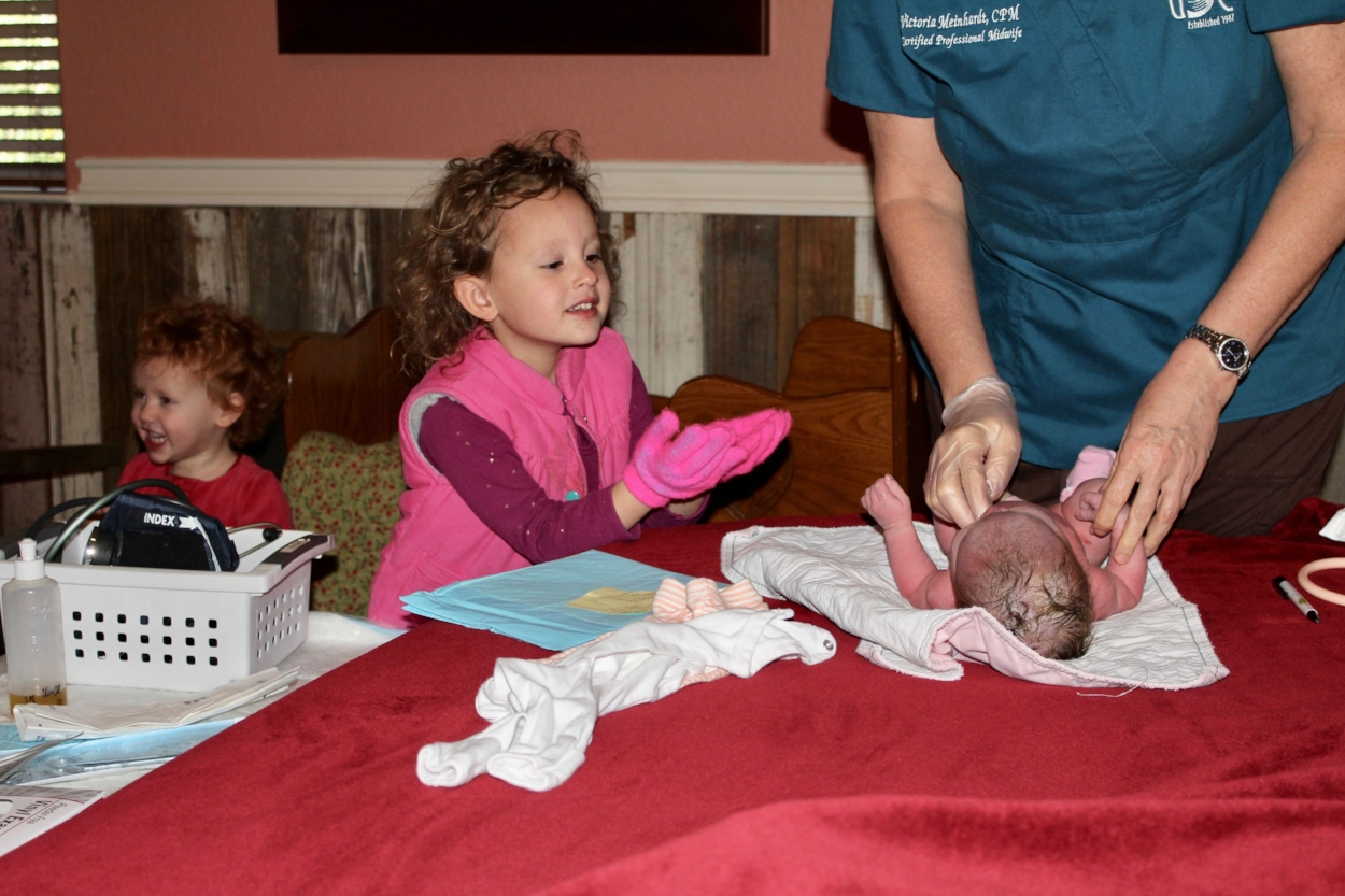 That first-born baby looking on while the fourth-born is getting vitals checked. Olivia, number three, is the photo bomber.