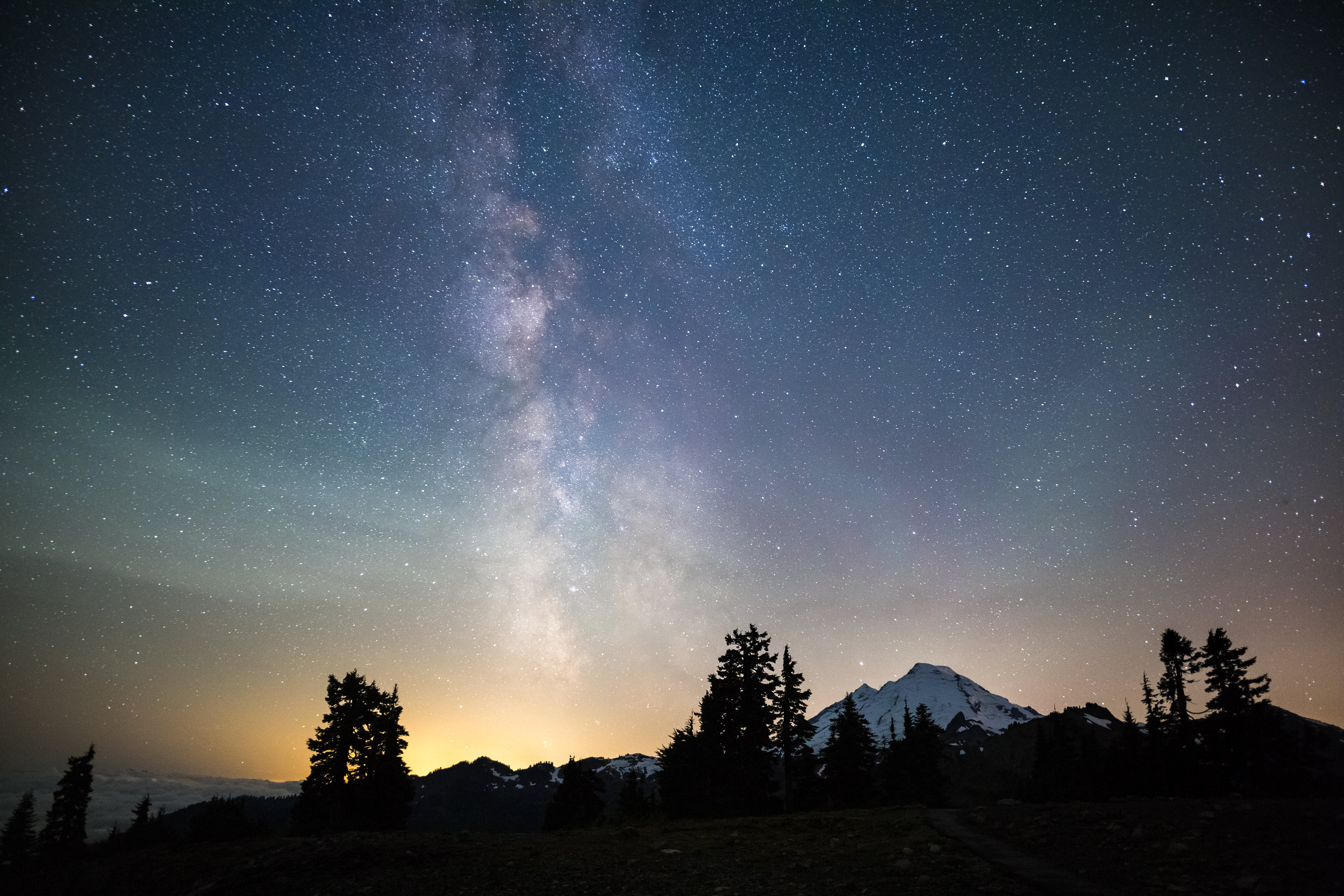 The distant Mount Baker towers over the landscape as the Milky Way streaks across the sky. The distant city lights of the greater Seattle area glow on the horizon.