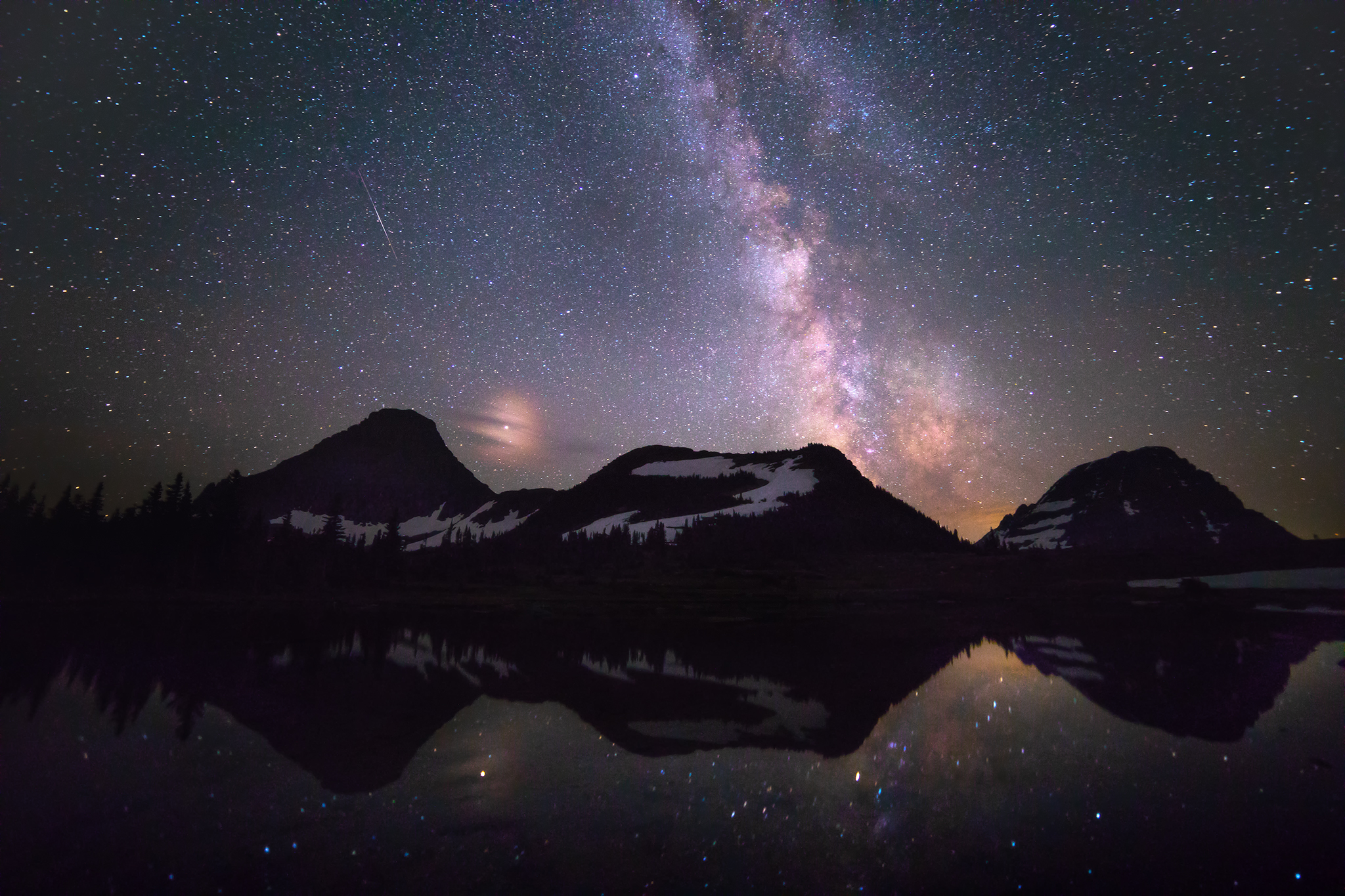 The night sky seen above Glacier National Park in Montana, USA. In addition to the Milky Way, Mars can be seen near the peak of the mountain on the left. A single shooting star is visible as well in the sky above the left mountain peak.