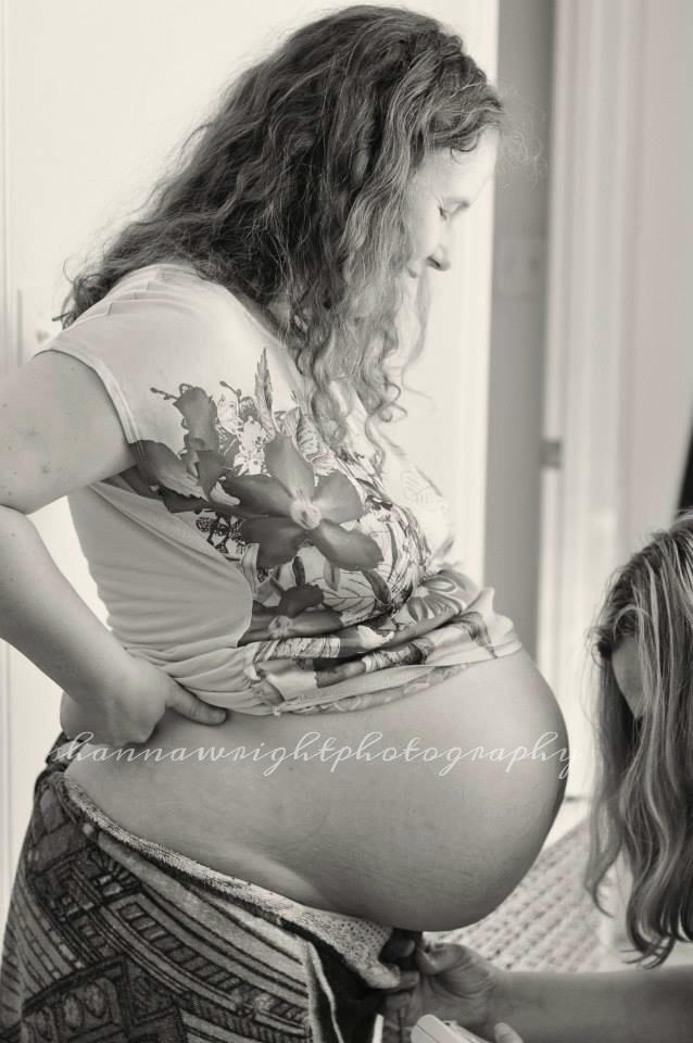 Midwife Liz listening to baby's heartbeat with a handheld doppler.   Image provided by Shanna Wright Photography