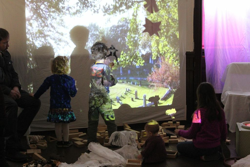 Children build with blocks and play with shadow puppets, in a space enhanced by a video projection on the wall.