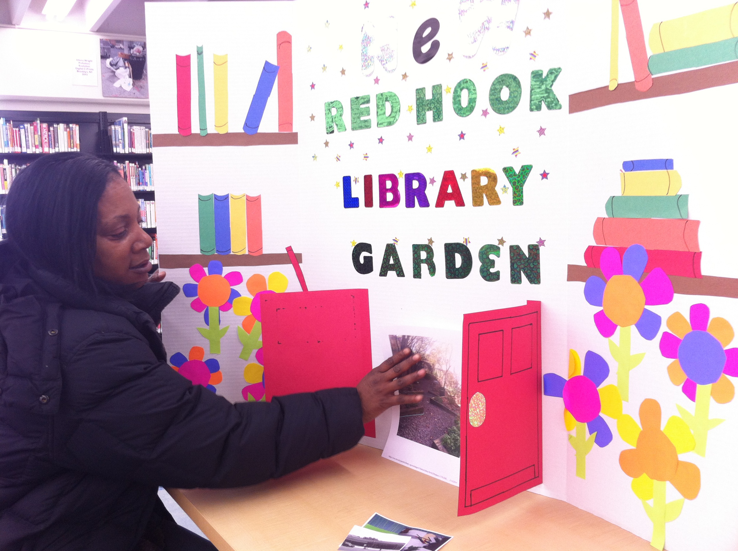 """Sheryl Braxton, a Participatory Budget delegate in Red Hook, puts the finishing touches on the poster she and other volunteers created for the Expo that happened in Sunset Park on March 15. At Find & Seek we remember attending a few PBNYC meetings in Fall of 2013, at which time we threw """"Library Garden restoration"""" into the pool of ideas. Our wildest dreams have come true: something we (and Sandra Sutton, Director of the Red Hook branch) presented as worth of city funds has made it onto the official ballot, and might just win some funding!  Learn more about PBNYC."""