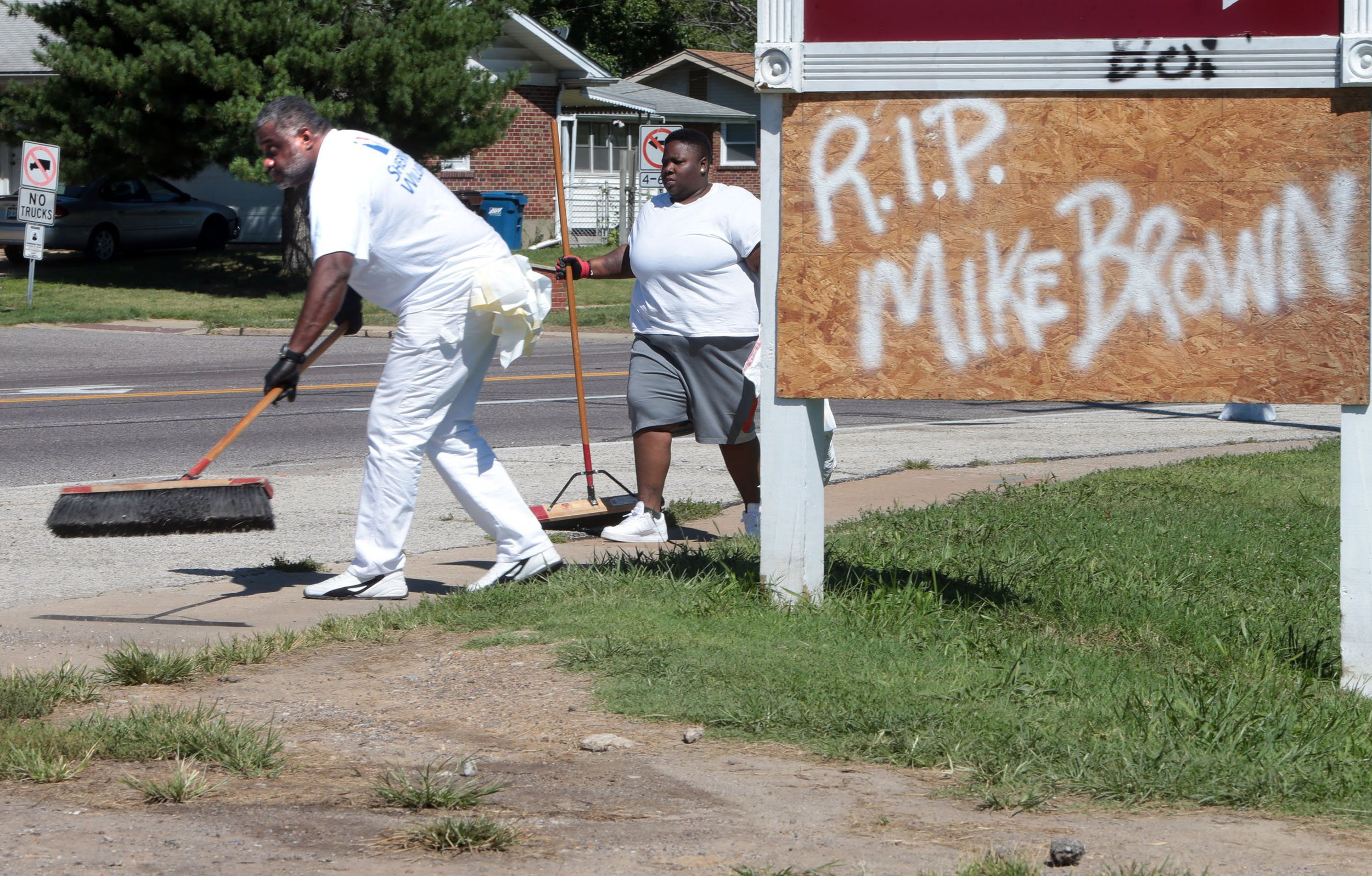 """""""I wanted to come out and help bring this community back together. And with being older, I wanted to set an example and inspire leadership to the youth,"""" said Anthony Clark of Arnold (far left) who helps clean up trash on Wednesday, Aug. 13, 2014, on W. Florissant Ave. in Ferguson. More than 100 volunteers came together to send a positive message to the community by cleaning up the businesses and areas that were damaged by looting and riots on Sunday night. Behind Clark is volunteer Keeosha Conely of Ferguson.  Photo by Laurie Skrivan, lskrivan@post-dispatch.com"""