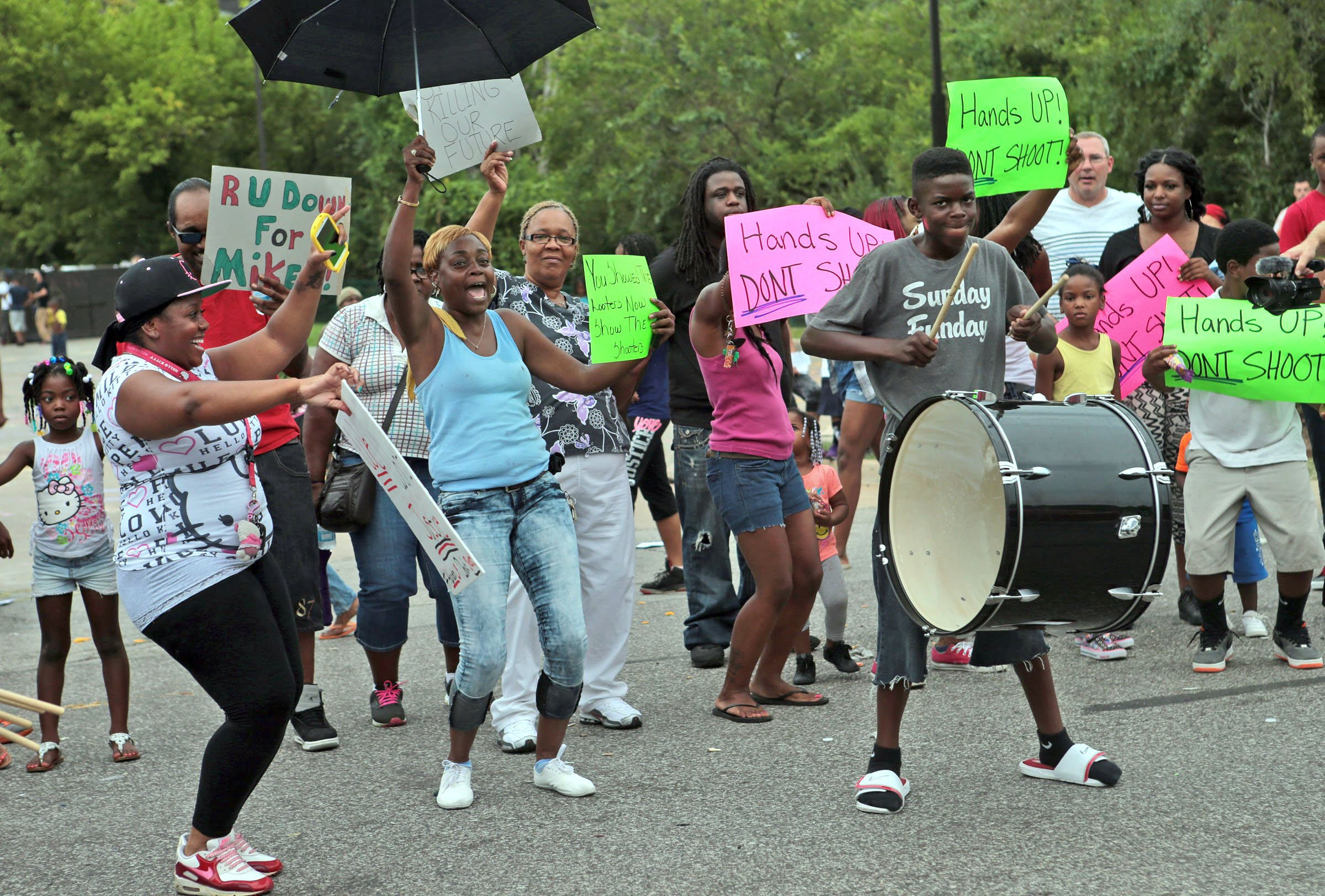 """""""I am loving the unity out here,"""" said Kim Harris (center) who dances to the drumming of Avery Gales, 13, with protestor Jasmine Davis (left) on Friday, Aug. 15, 2014, in the parking lot of the burned QuikTrip.  Photo by Laurie Skrivan, lskrivan@post-dispatch.com"""