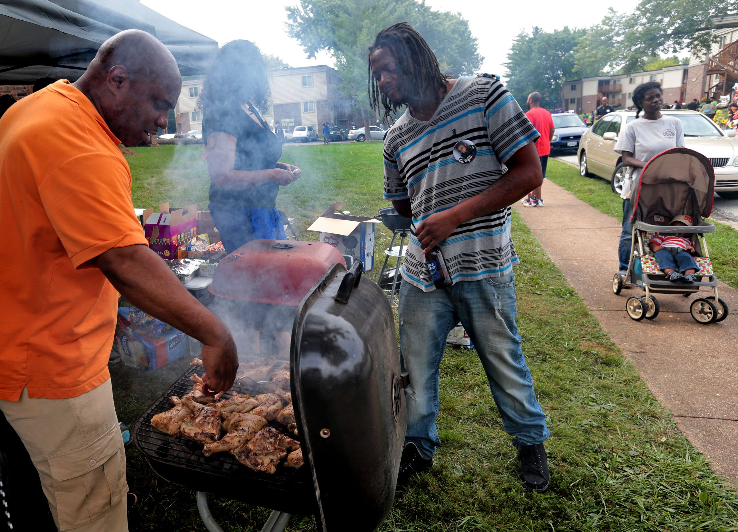 """""""I live here but I am contributing too. I brought stuff over. I wanted to give back, to do anything to promote the unity I am feeling. Anything to promote anything positive,"""" said Devon Stone, (left), who watches Kevin Ephron of Florissant aka """"The Grillmaster"""" cook up BBQ for residents on Saturday, Aug. 15, 2014, inside Canfield Green apartment complex. Ephron's sister Yolando Miller organized a tent inside the compex offering free drinks, food, school supplies, diapers for the families inside the complex.  Photo by Laurie Skrivan, lskrivan@post-dispatch.com"""