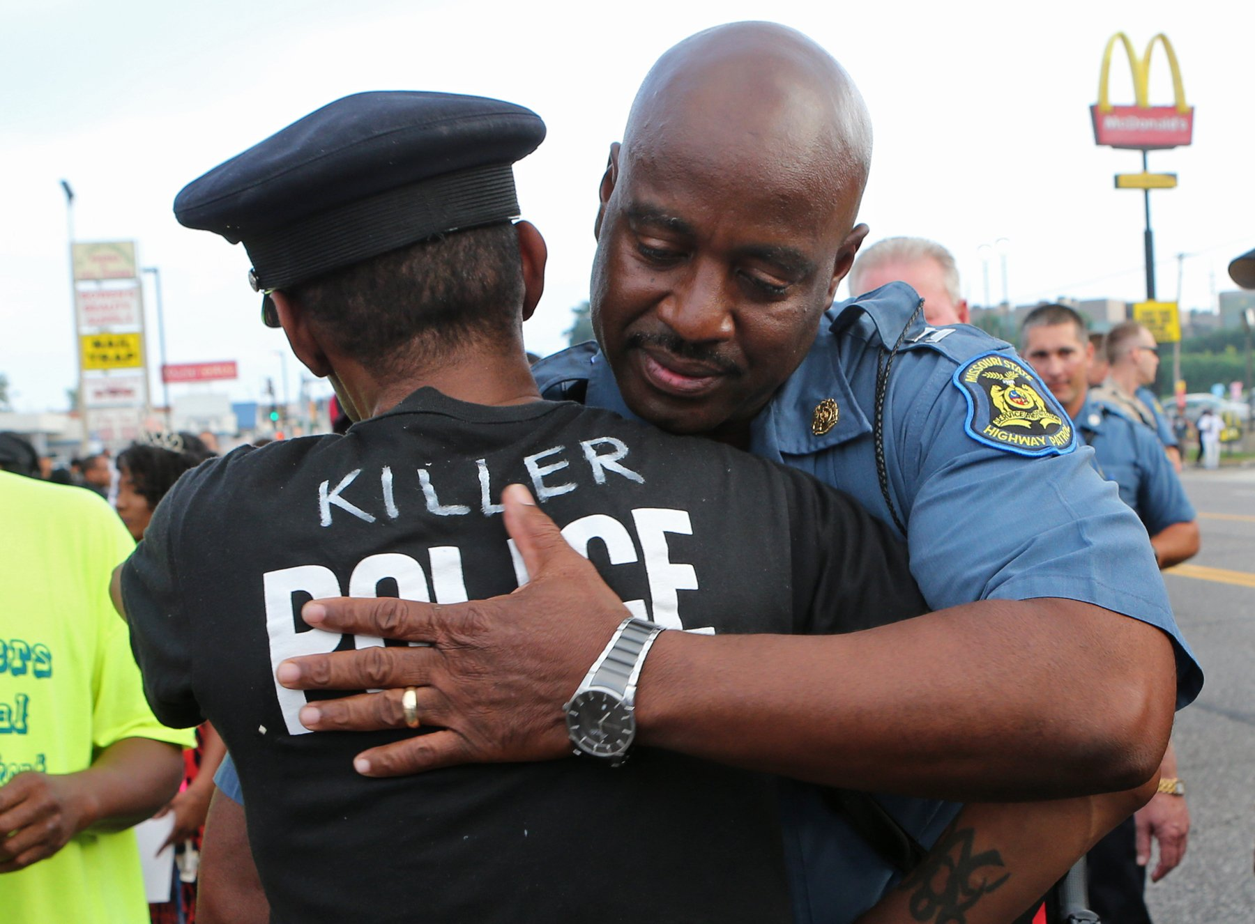 """Mo. Highway Patrol Capt. Ron Johnson hugged Adrian (who wouldn't give his last name) in Ferguson on Sunday afternoon, Aug. 17, 2014, on W. Florissant. Adrian said that he was a St. Louis city police officer for ten years. He said he could see the issue from both sides but he said the cop (Darren Wilson) went way beyond the use of prudent force. """"He had many more options to him before he went for his gun,"""" Adrian said. """"If the suspect was too big for him, he should have called for backup,"""" he said. """"I wake up crying every day,"""" he said.  Photo by J.B. Forbes, jforbes@post-dispatch.com"""