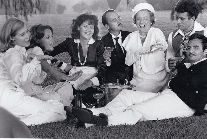 The cast of AT LONG LAST LOVE (l. to r.): Cybill Shepherd, Madeline Kahn, Eileen Brennan, John Hillerman, Mildred Natwick, Duilio Del Prete, and Burt Reynolds.