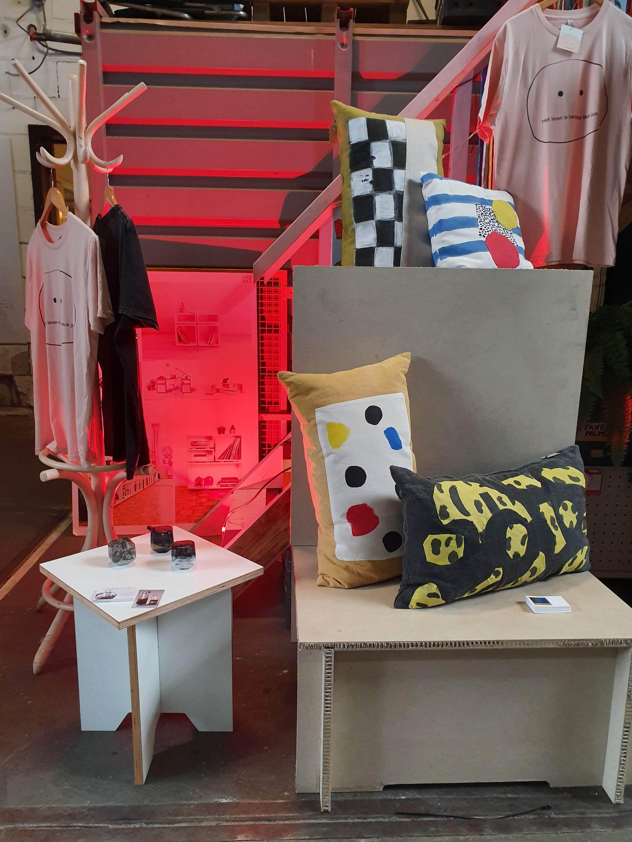 Werk van Vicky Pylorides (kussens) , Jule Cats (Paperweights), Studio Davero (meubels) en Malou Cohen (tshirts)