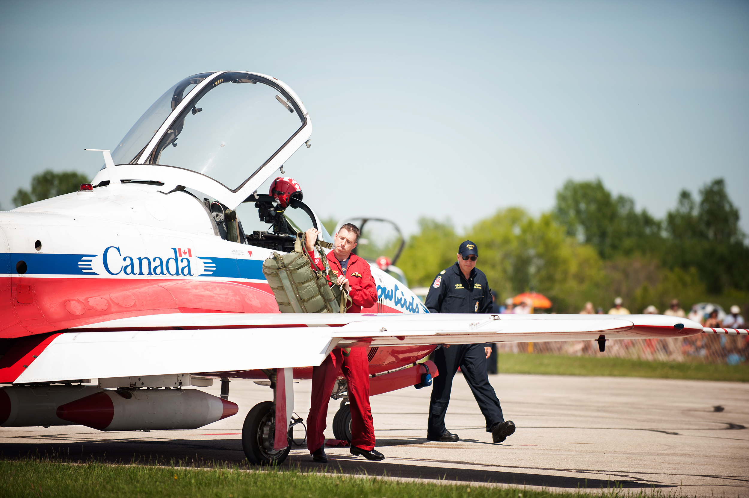Snowbirds Pilot puts his parachute on after giving it a check over