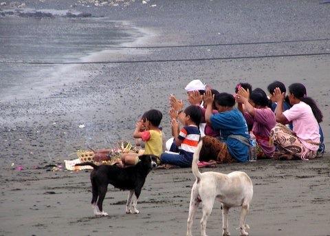 Family praying on beach, Pemuteran Bay, Bali