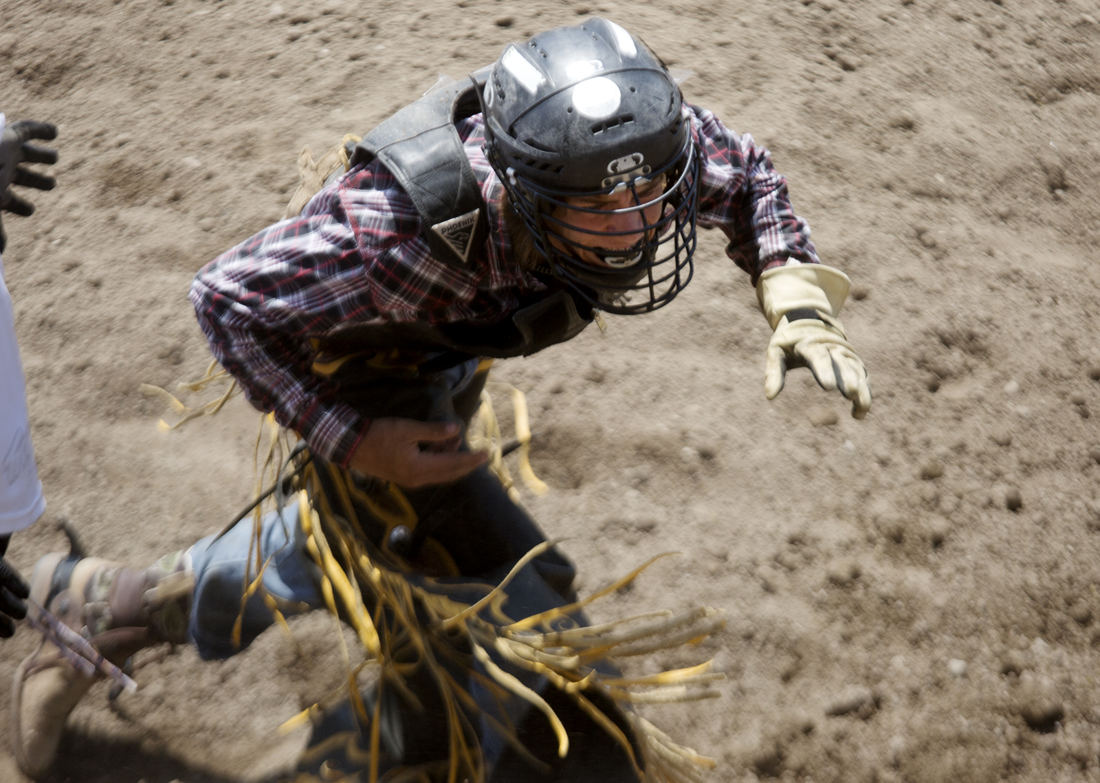 Colton Kent clutches his abdomen and runs towards the fence after his run in Little Britches Senior Bull Riding competition Friday, July 26 2013 at the Pueblo State Fairgrounds. Kent fell off before the eight second buzzer, and was stepped on by his bull.