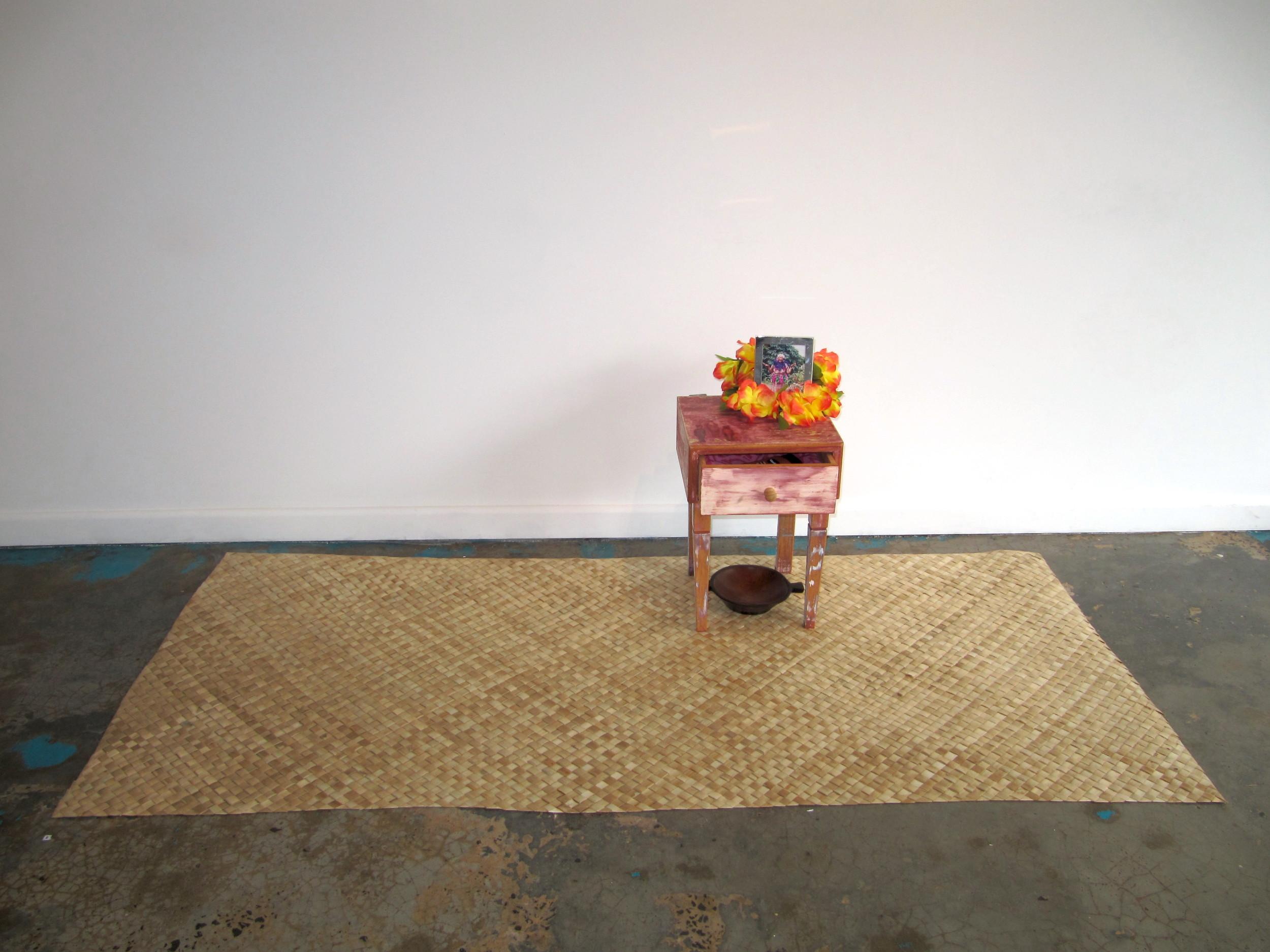 'O 'ie fala mo la'u tinā Nātia | Fine mats for my grandma Nātia, Léuli Eshraghi, pandanus mat, wooden table, tānoa kava bowl, photo frame, 'ula lei, cacao cream, 'ie lavalava, 2012