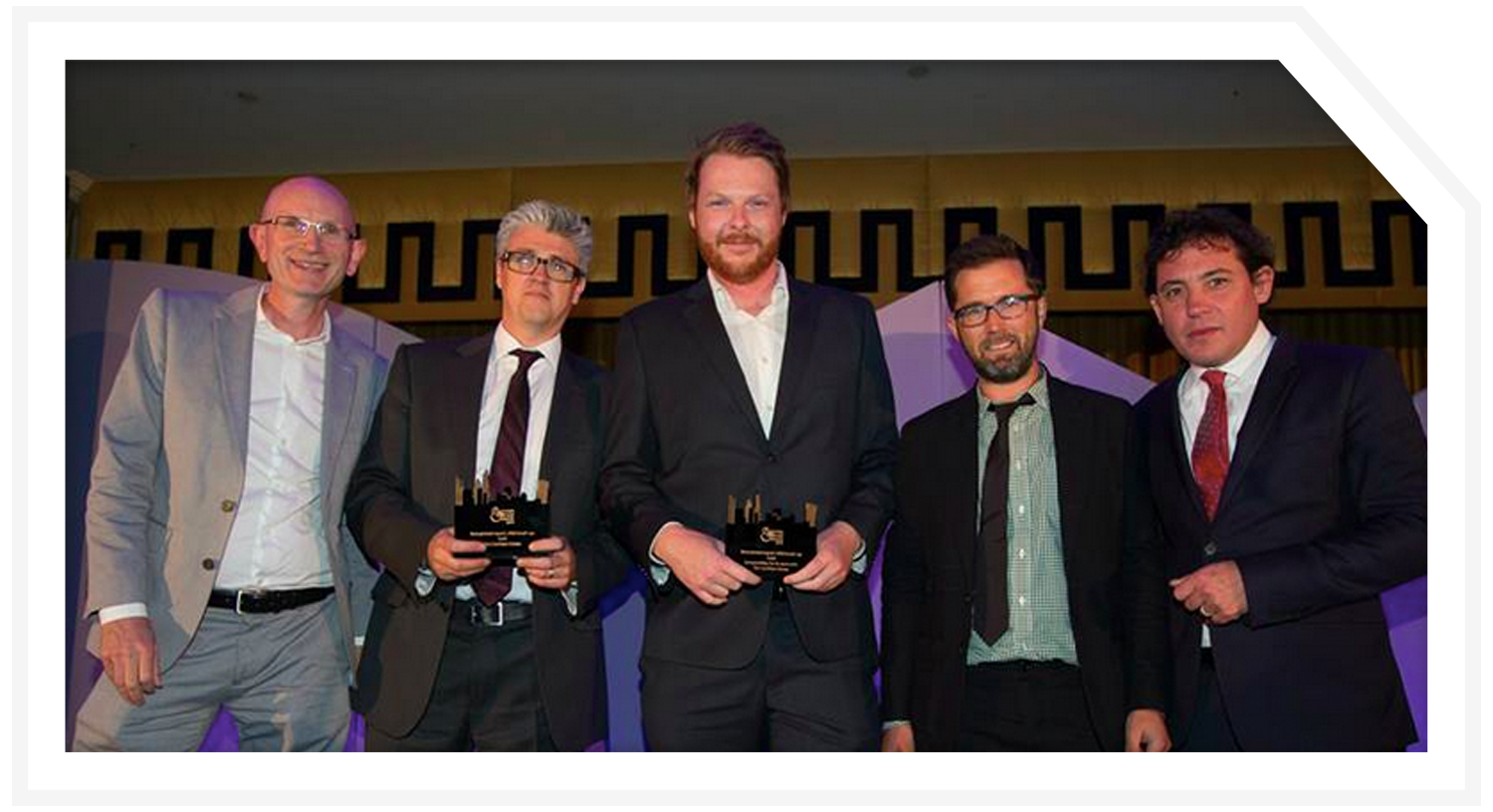 Rocksalt's Paul Nolan (left) and host Simon Jack (right) with worthy winners from Cambian Group