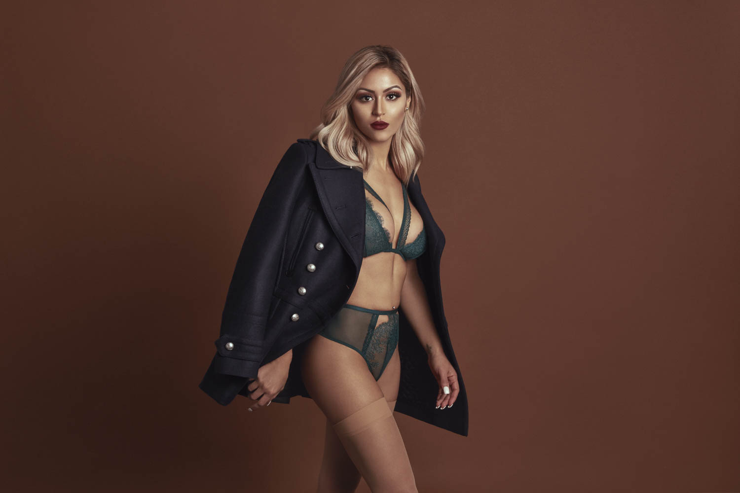 Blonde woman in blue coat and green bra and panty set