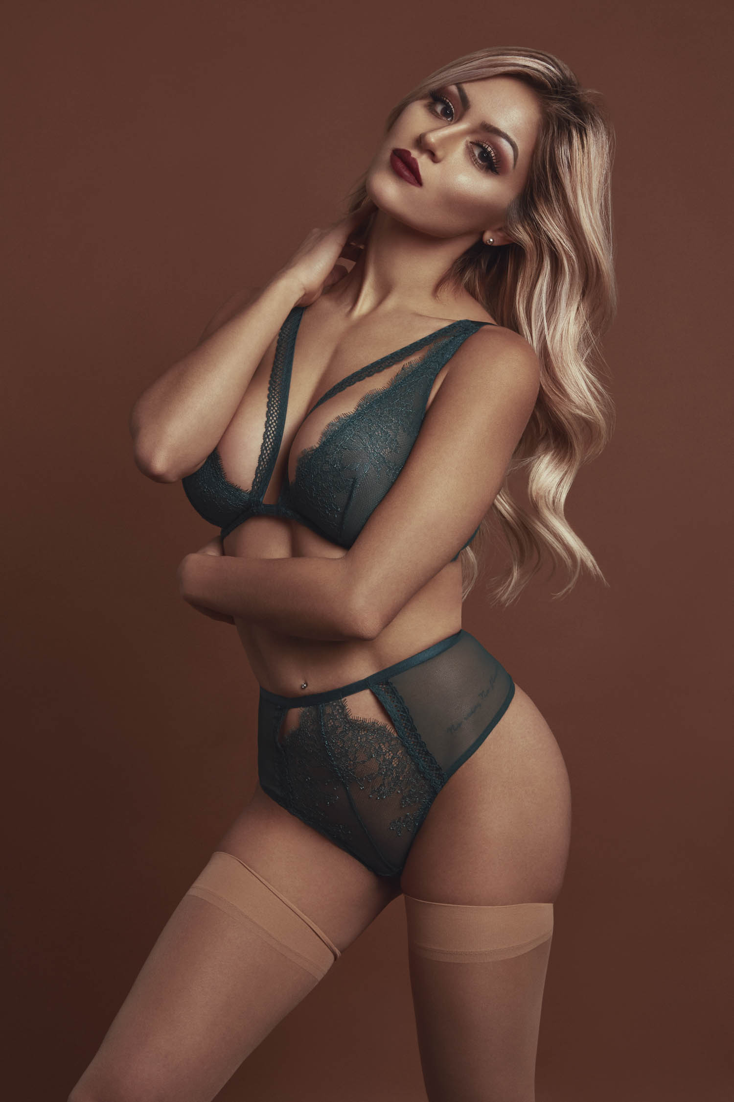 Blonde woman in a green bra and panty set with nude tights