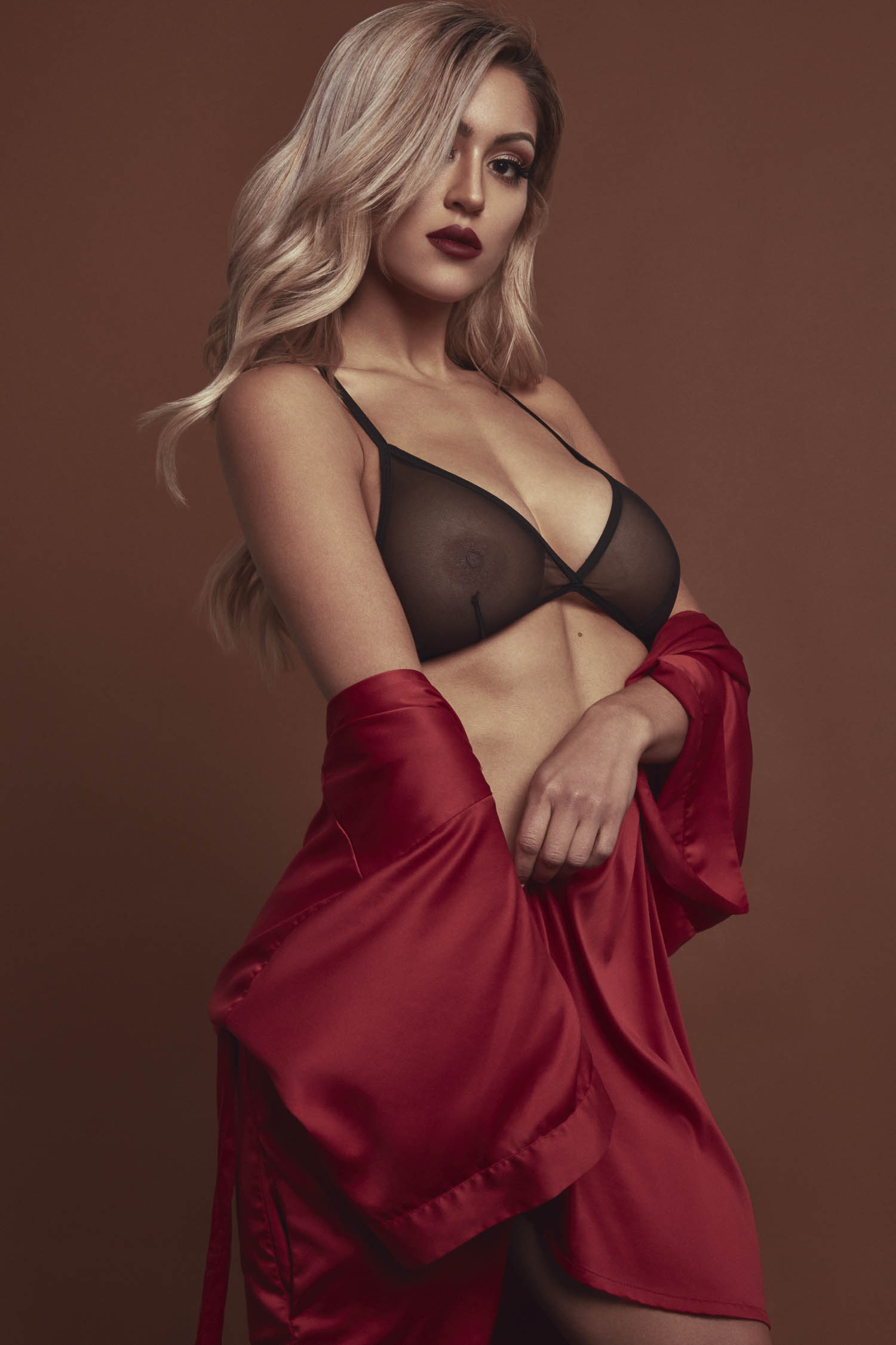 Blonde woman in a black bra and red satin robe