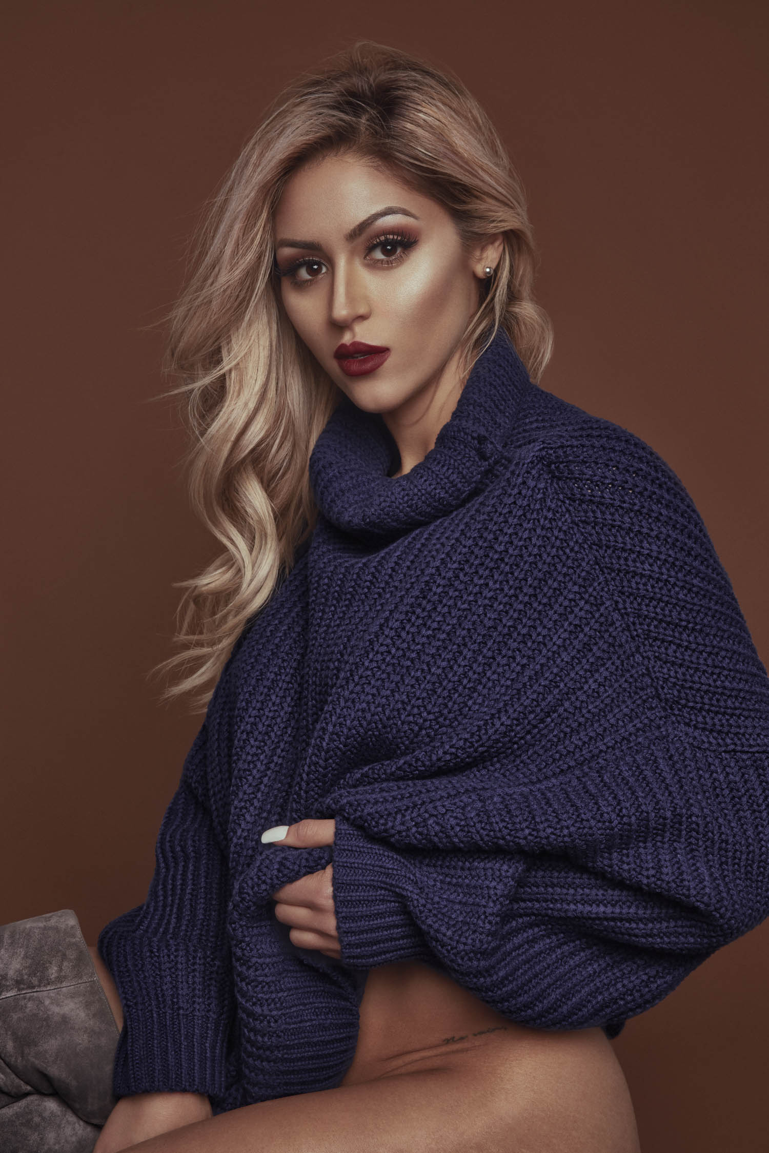 Blonde woman with red lipstick in a blue cowl neck oversized sweater