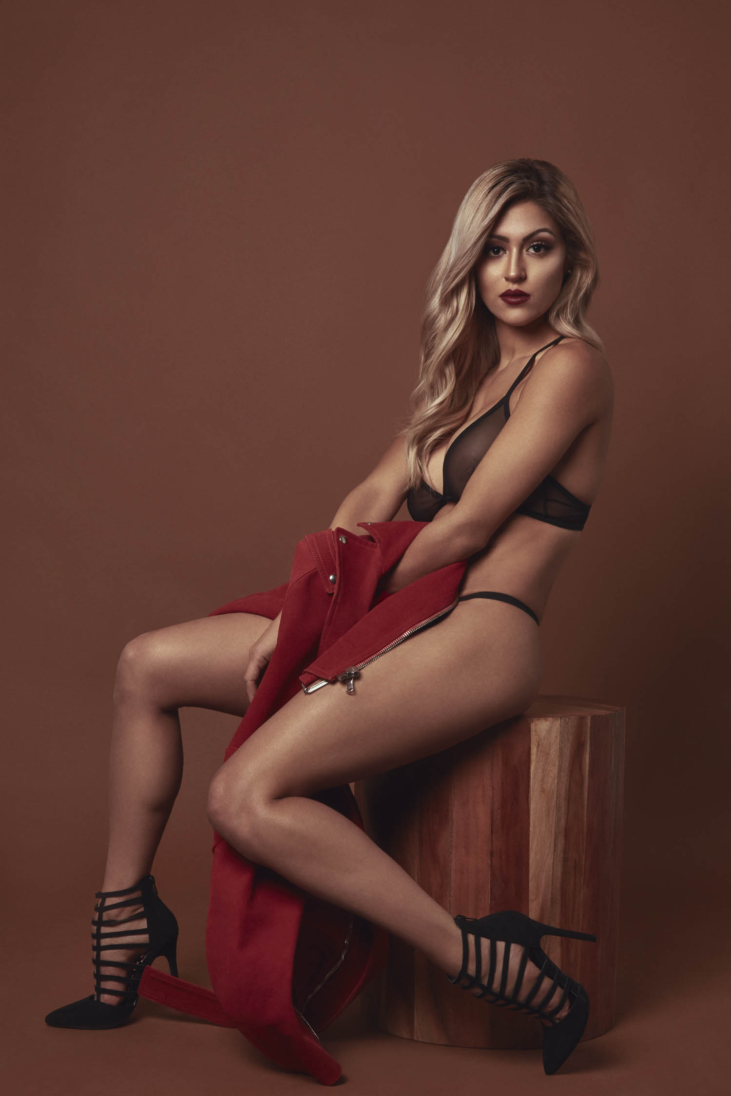 Blonde woman sitting on a wooden stool with red coat and black stilettos