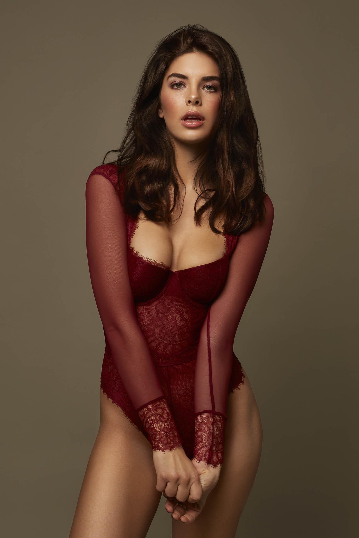 Brunette model wearing long sleeve burgundy jumpsuit