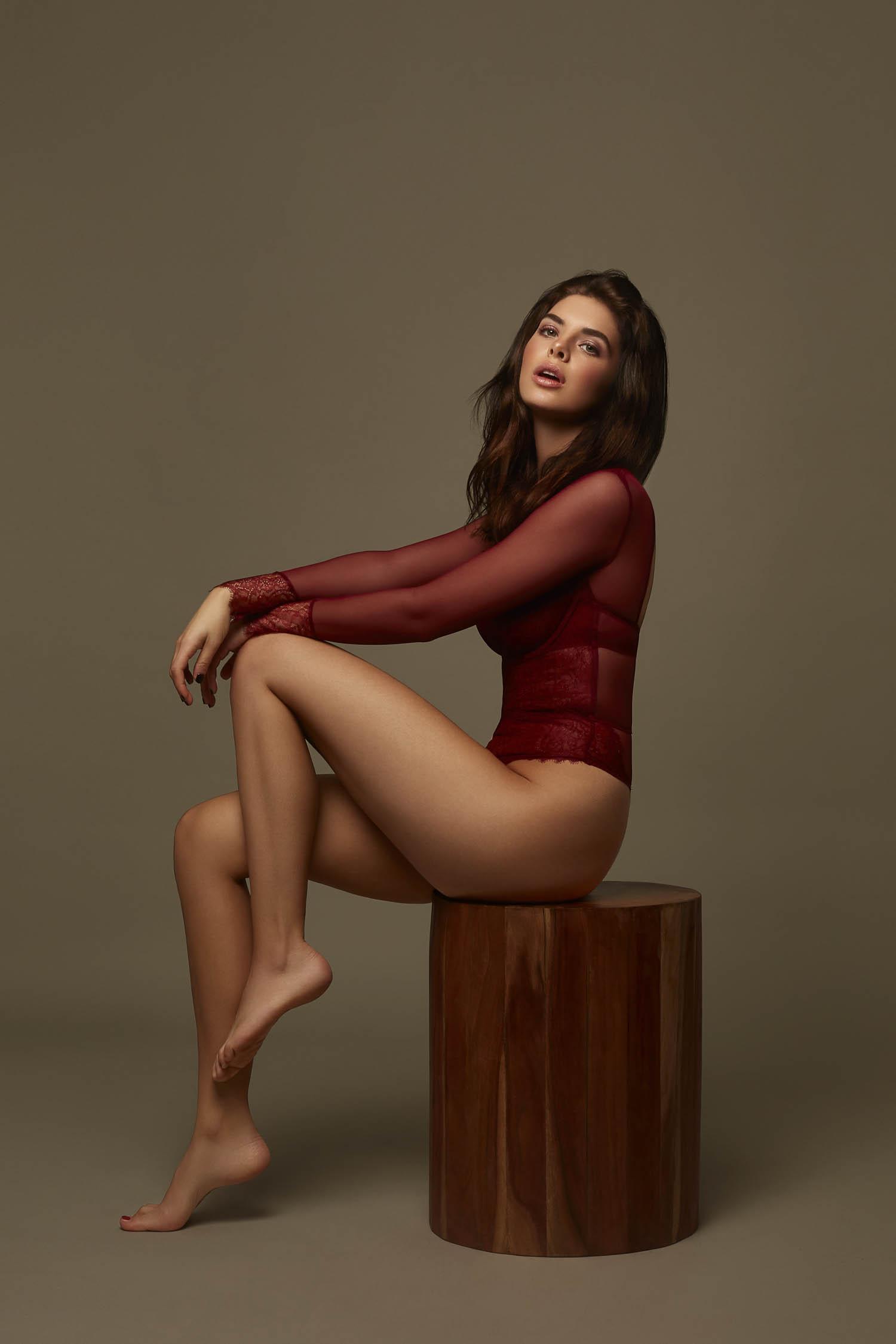 Brunette wearing burgundy long sleeve bodysuit sitting on a wooden stool
