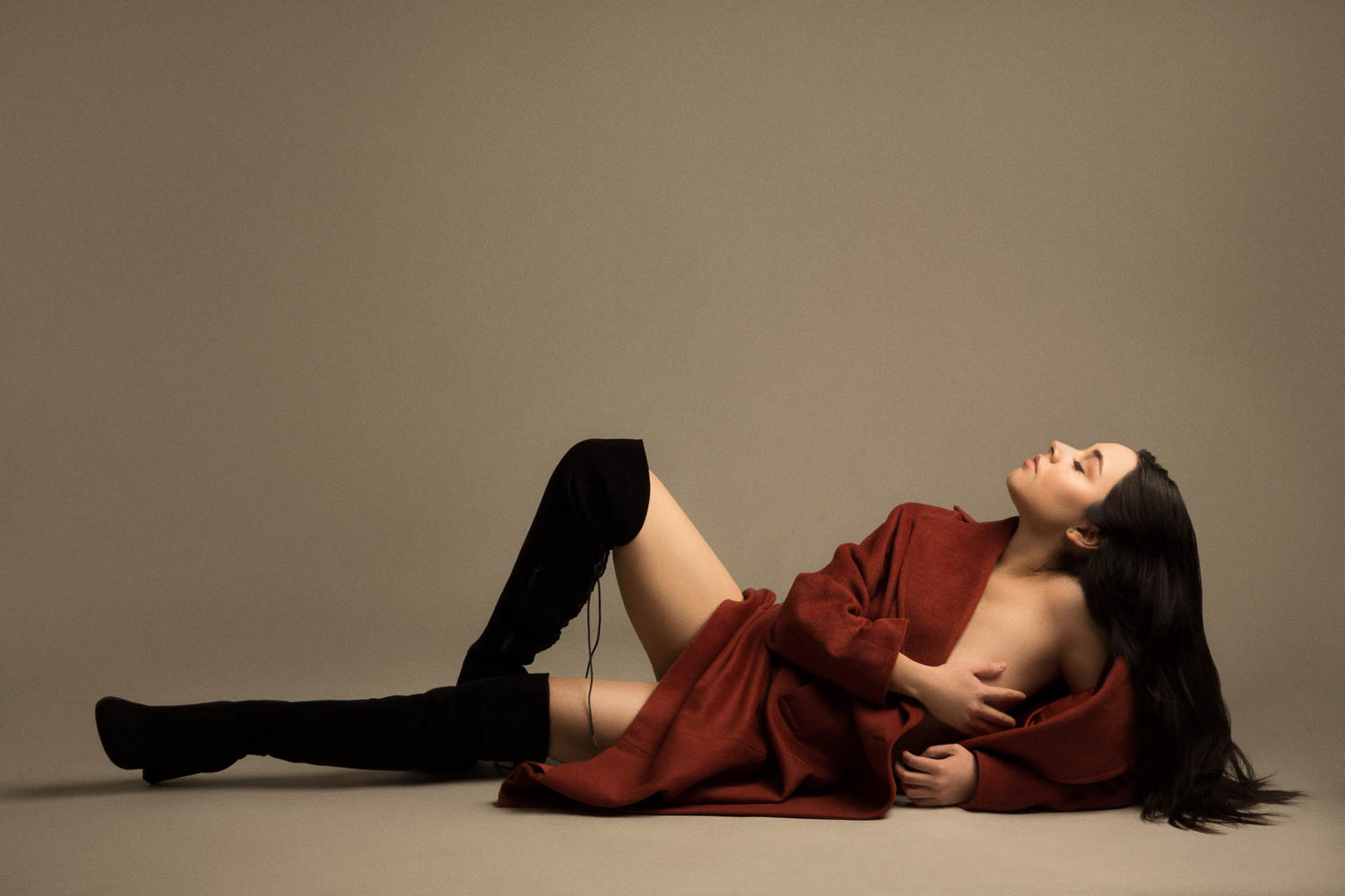 model with long hair laying down with thigh high black boots and an ochre trench coat