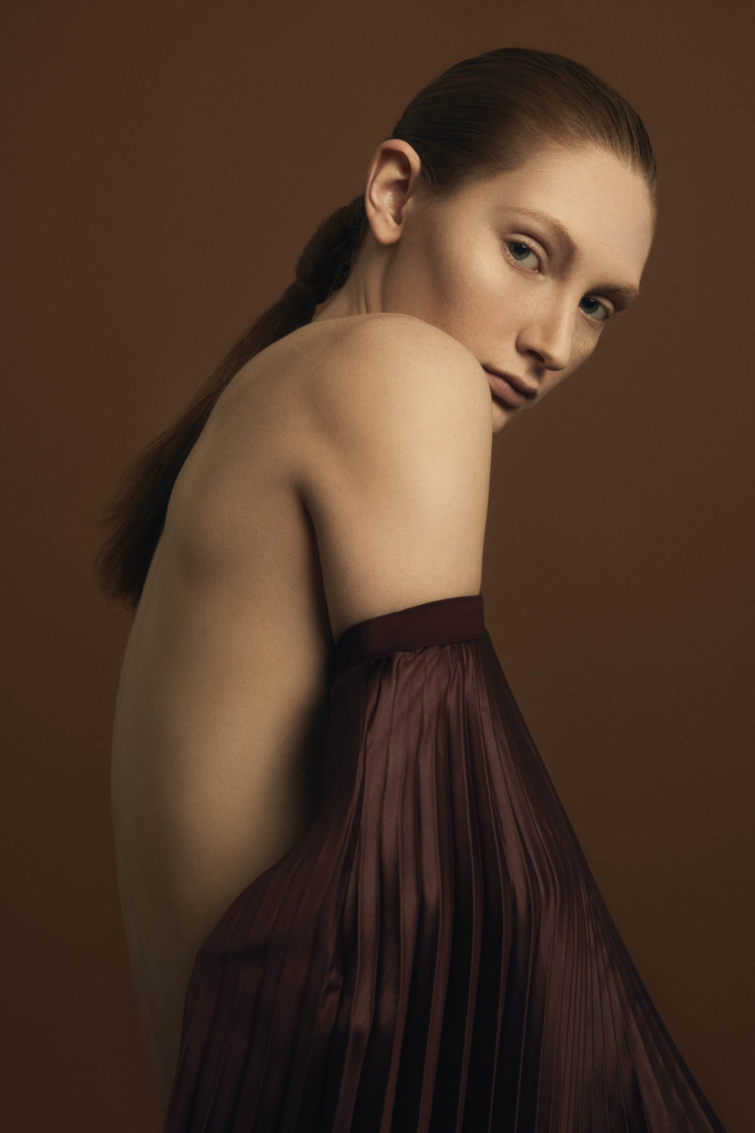 Model with red hair and natural makeup in brown accordion satin