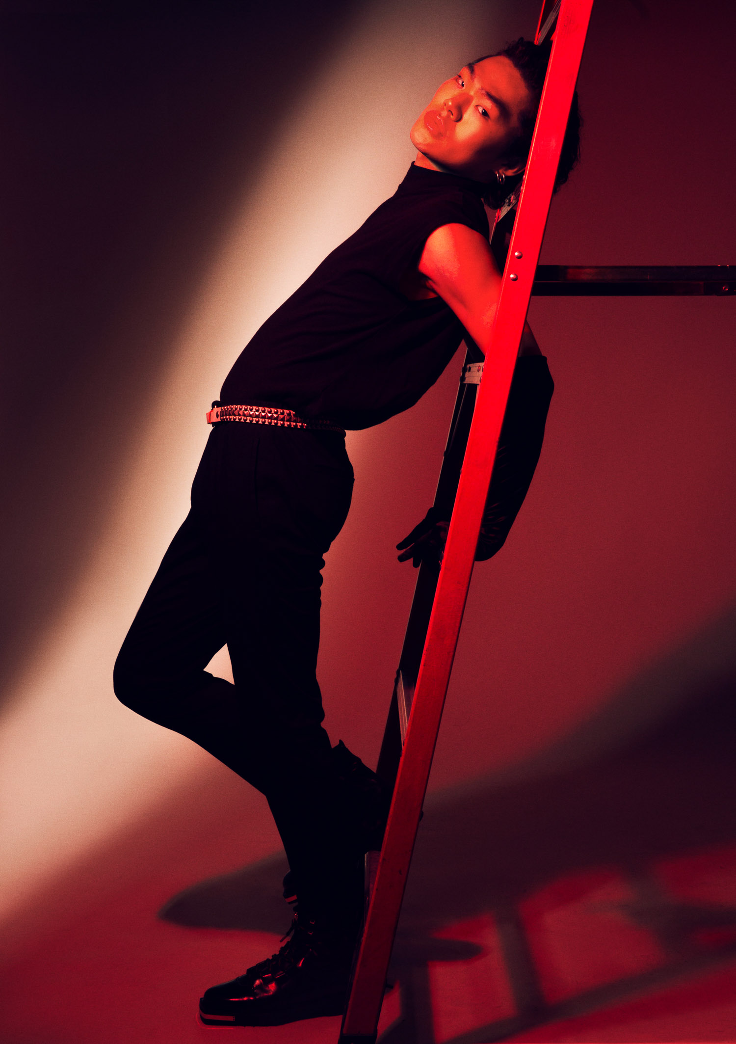 Man in red light leaning on ladder.