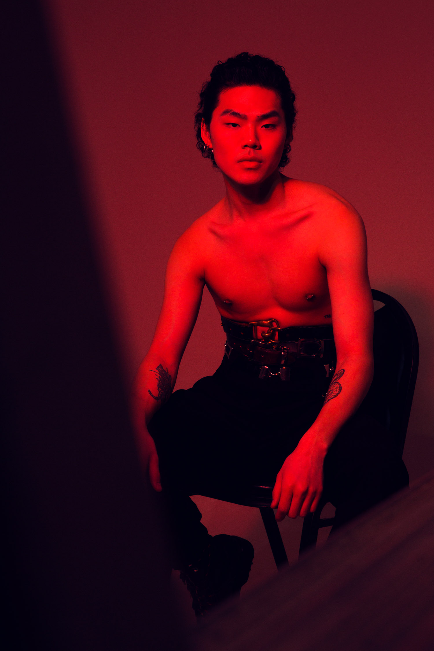 Shirtless man in red light sitting on a chair.