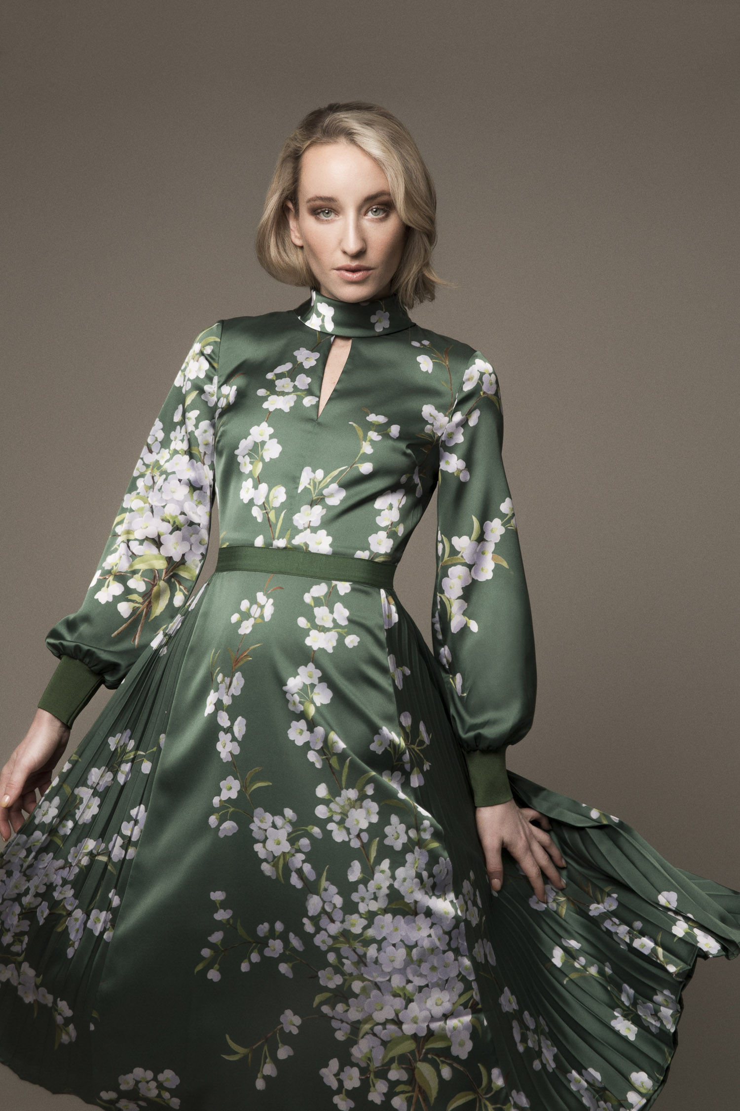 Model in a green Ted Baker dress with long sleeves