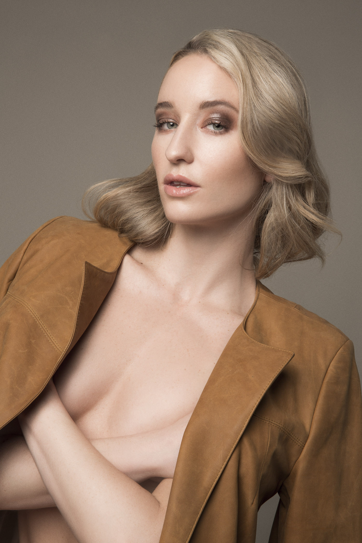 Blonde model in a luxury leather trenchcoat