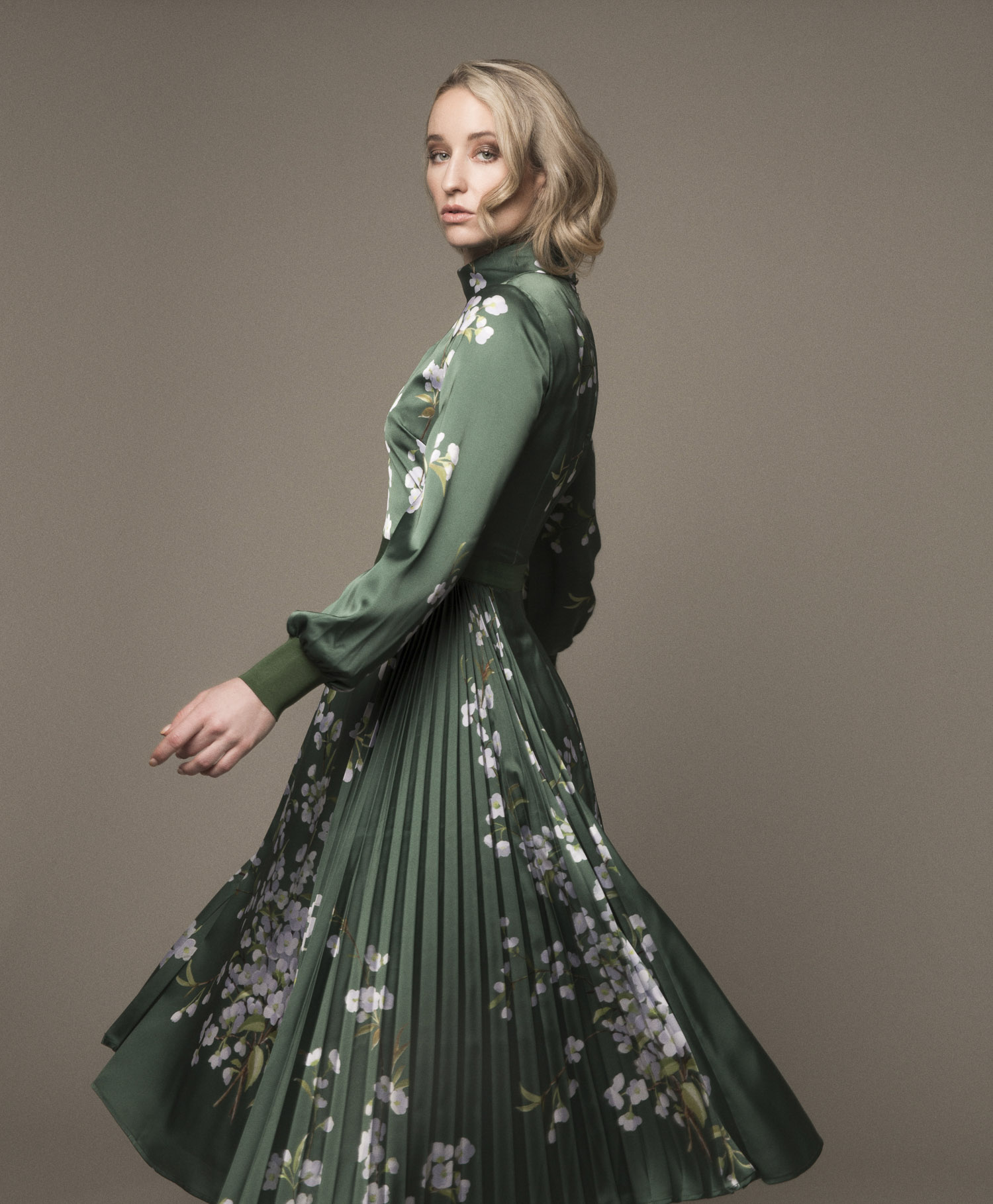 Model spinning in a green Ted Baker dress